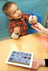 Reco Capparelli, 3, uses an iPad to blow bubbles — part of an exercise on following directions during a therapy session with Wheaton-Warrenville Unit District 200 speech pathologist Nicole MacKinnon.