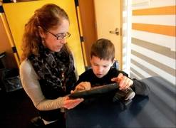 Vicki Brassil, elementary computer specialist at Giant Steps school in Lisle, works with Justin Hafner, 9, of Joliet, in using an iPad. The school, which teaches children with autism, has iPads available in each of its classrooms.
