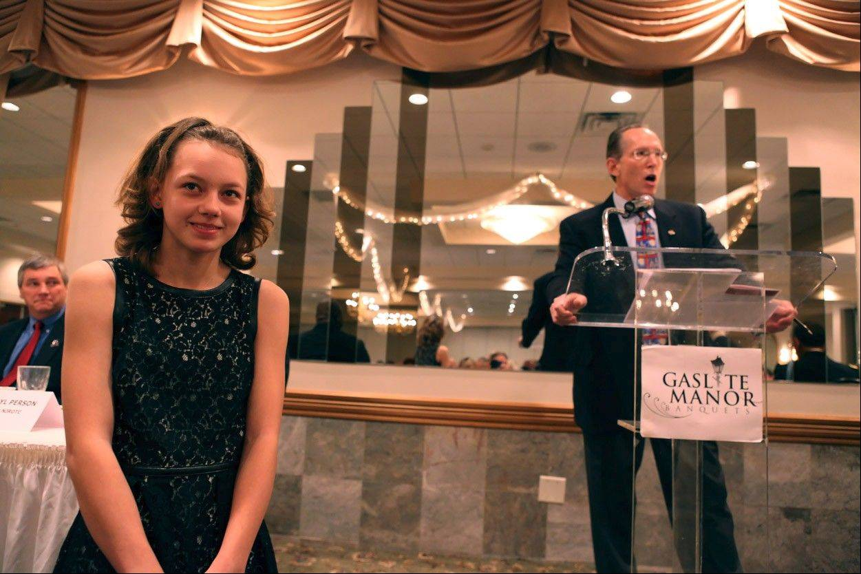 Herget Middle School student Madeline Bozik is introduced as a Brattin Civic Youth Award winner by Rotarian Tom Guzzardi at the recent community service awards ceremony.