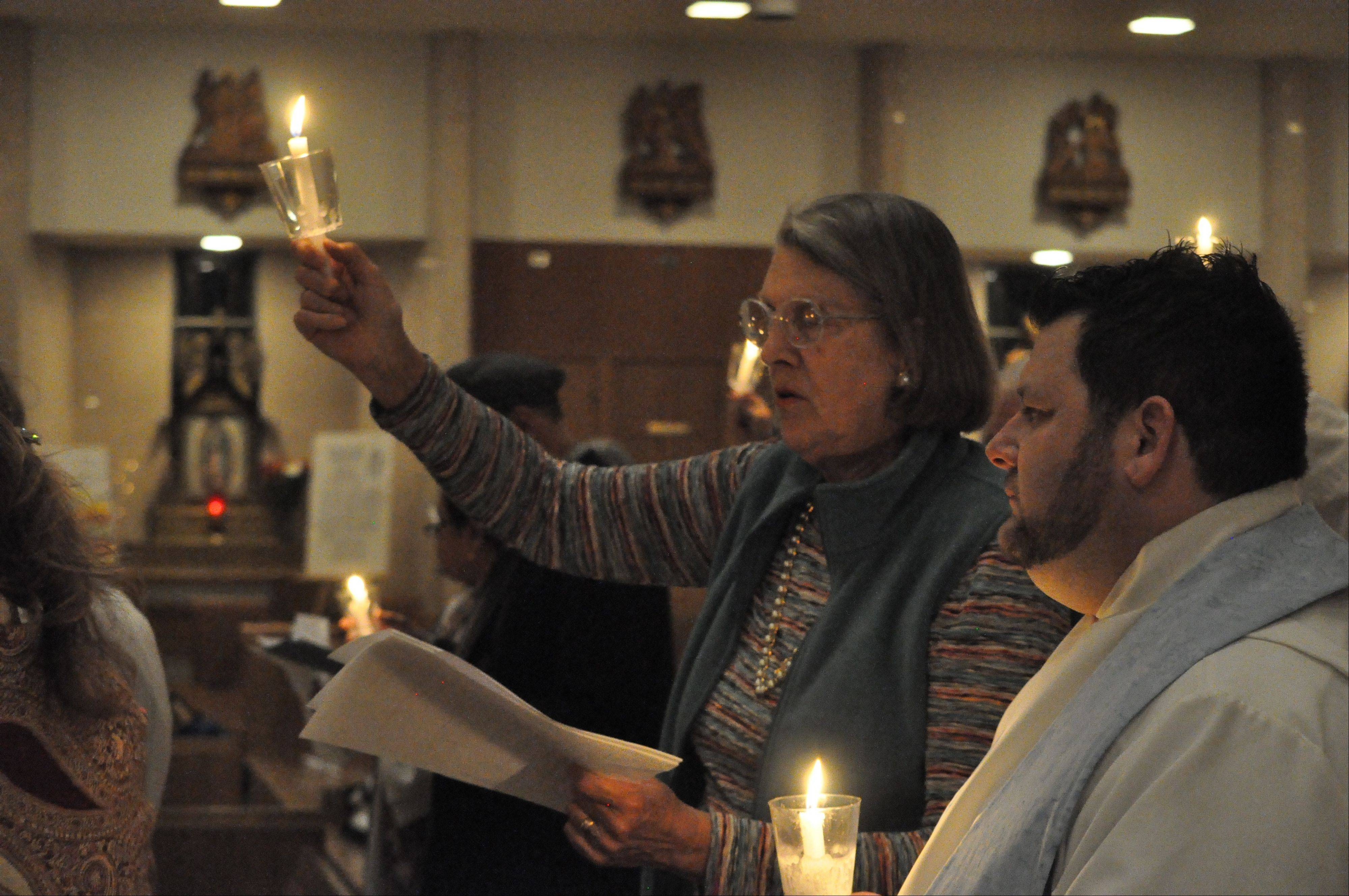 Emmy Lou John of Aurora's Wesley United Methodist Church, left, and the Rev. Brian Wise pastor at St. Mark's Lutheran Church, light candles for world peace and justice during a fifth annual Thanksgiving interfaith service at St. Joseph Catholic Church in Aurora Nov. 18.