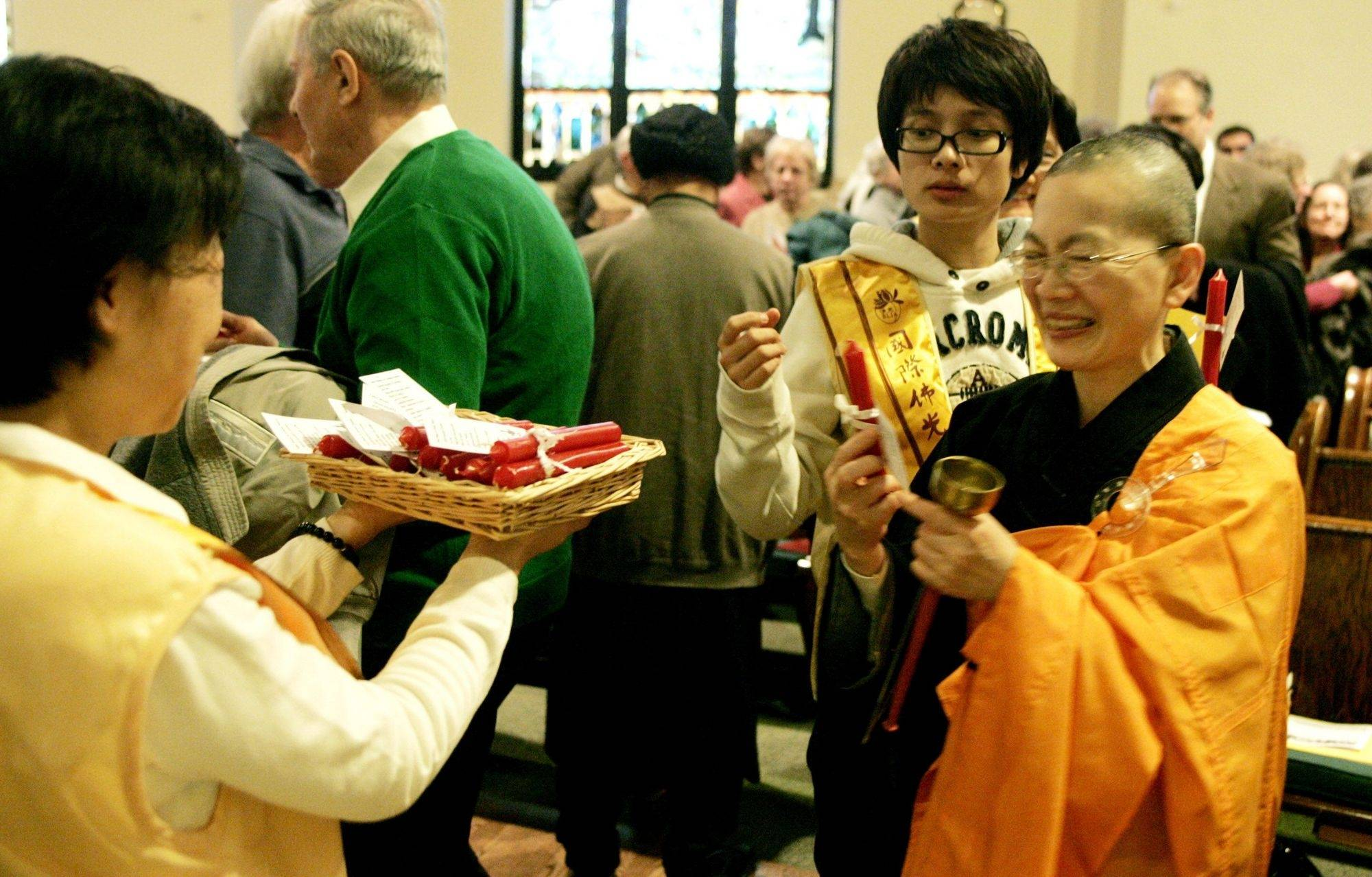 Venerable Miaotsan, right, picks up a candle as a way of committing herself to be a light of peace during the 5th Annual World Peace Day Interfaith Prayer Service on Sunday at First Congregational Church in Naperville.