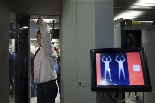 An employee of Schiphol stands inside a body scanner during a demonstration at a press briefing at Schiphol airport, Netherlands. On display the highlighted area shows an alert on possible forbidden items.