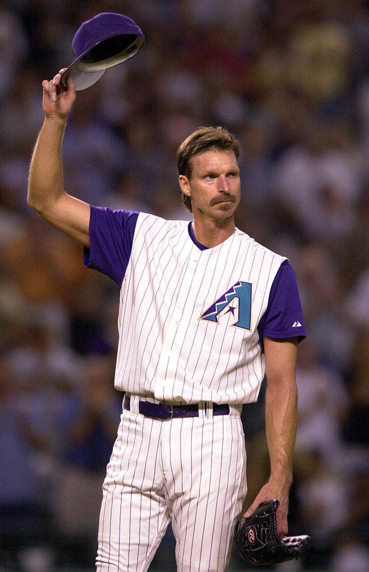 While pitching for the Arizona Diamondbacks in 2004, Randy Johnson acknowledges a standing ovation from the crowd after striking out the Colorado Rockies' Vinny Castilla to pass Steve Carlton for third place on the all-time strikeout list.
