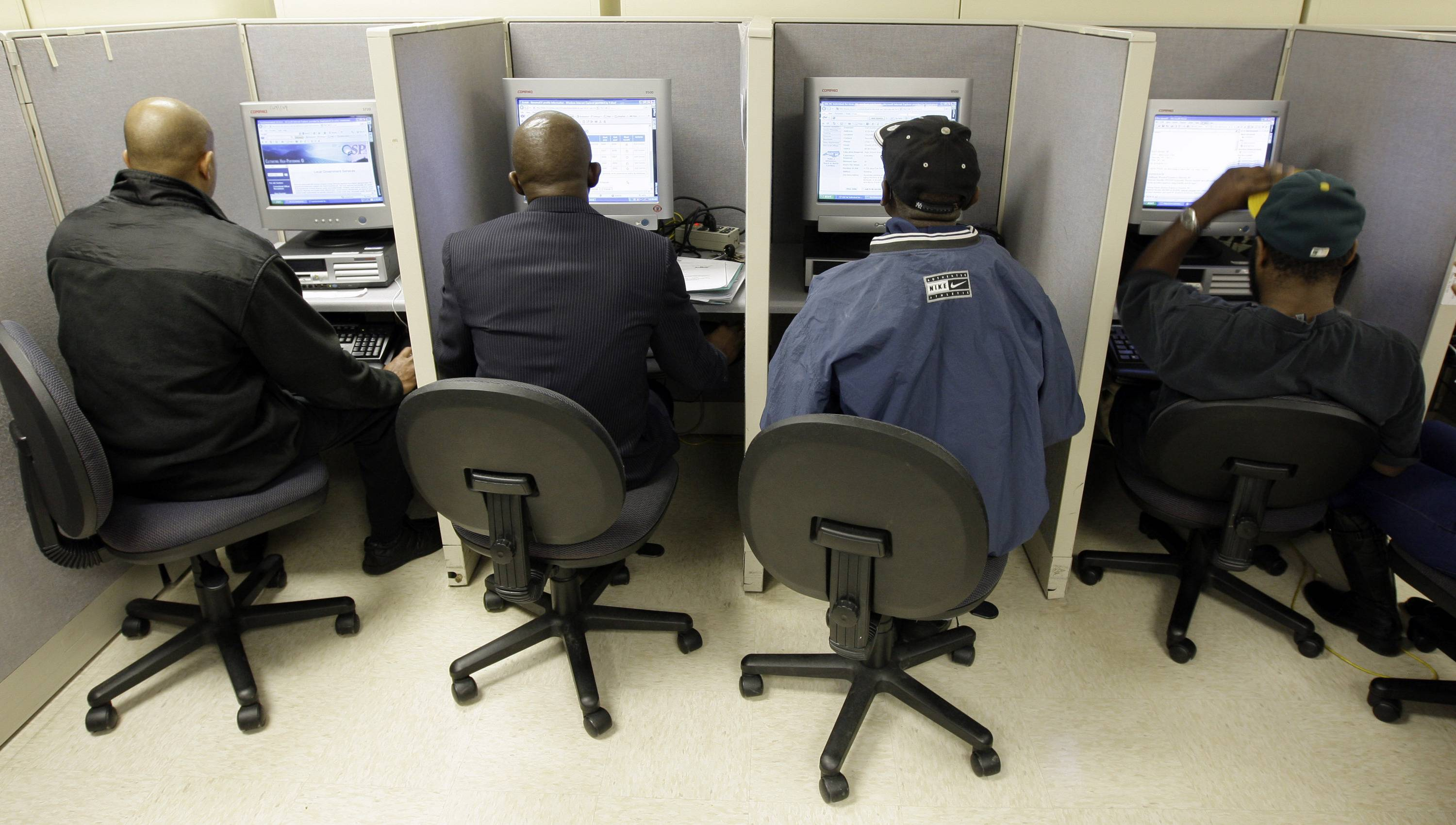 Job seekers search for jobs online at an Employment Security Commission office in Charlotte, N.C. The number of people claiming unemployment benefits for the first time barely rose last week, after two weeks of sharp drops.