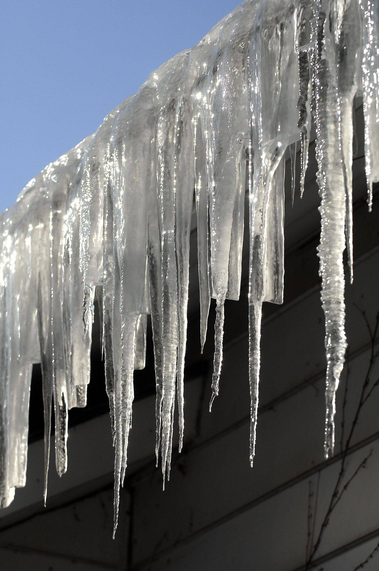 Breaking icicles can reduce the weight on gutters but ice damming will still occur.