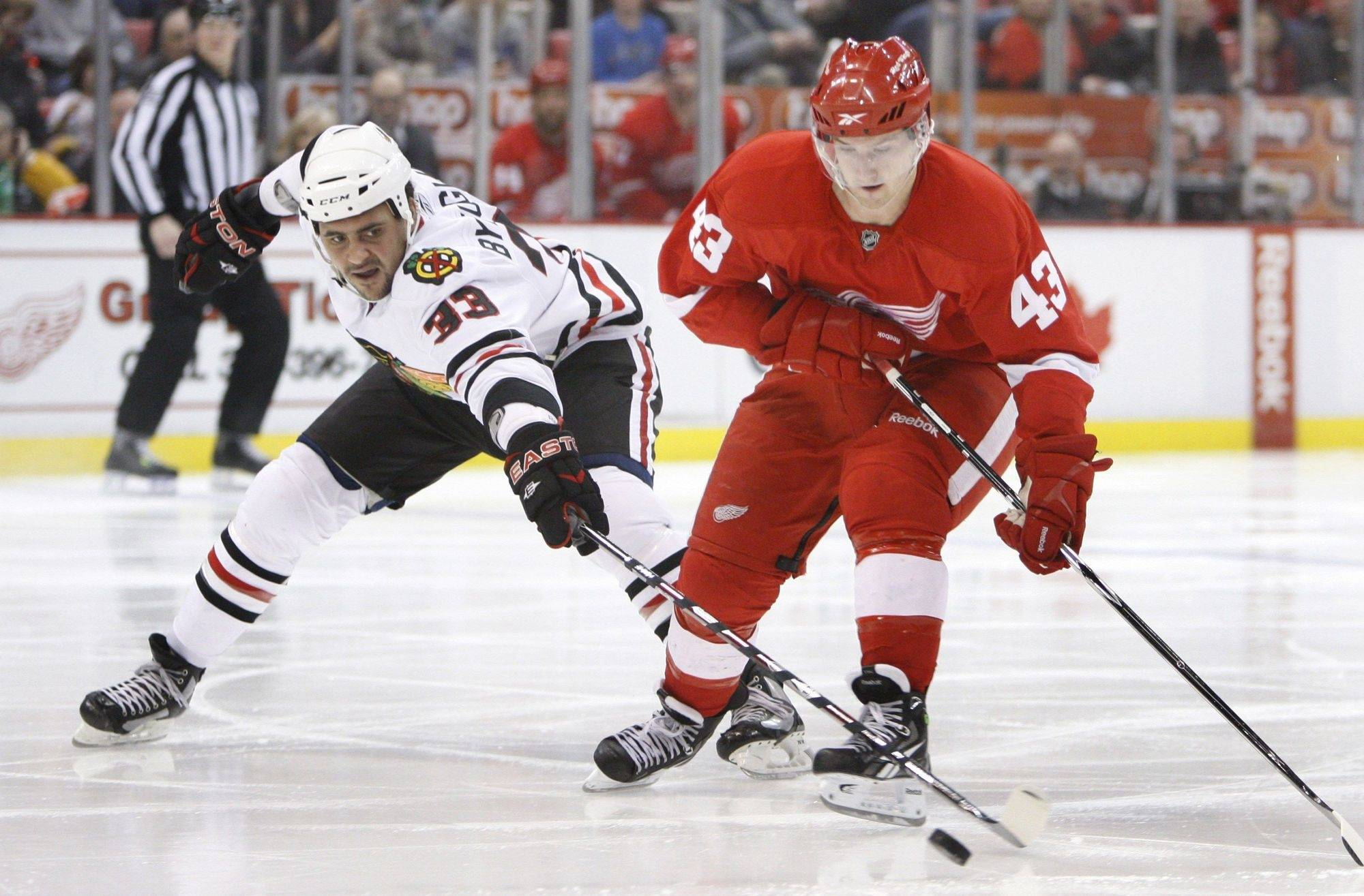 The Hawks' Dustin Byfuglien deflects the puck in front of Red Wings center Darren Helm on Sunday in Detroit.