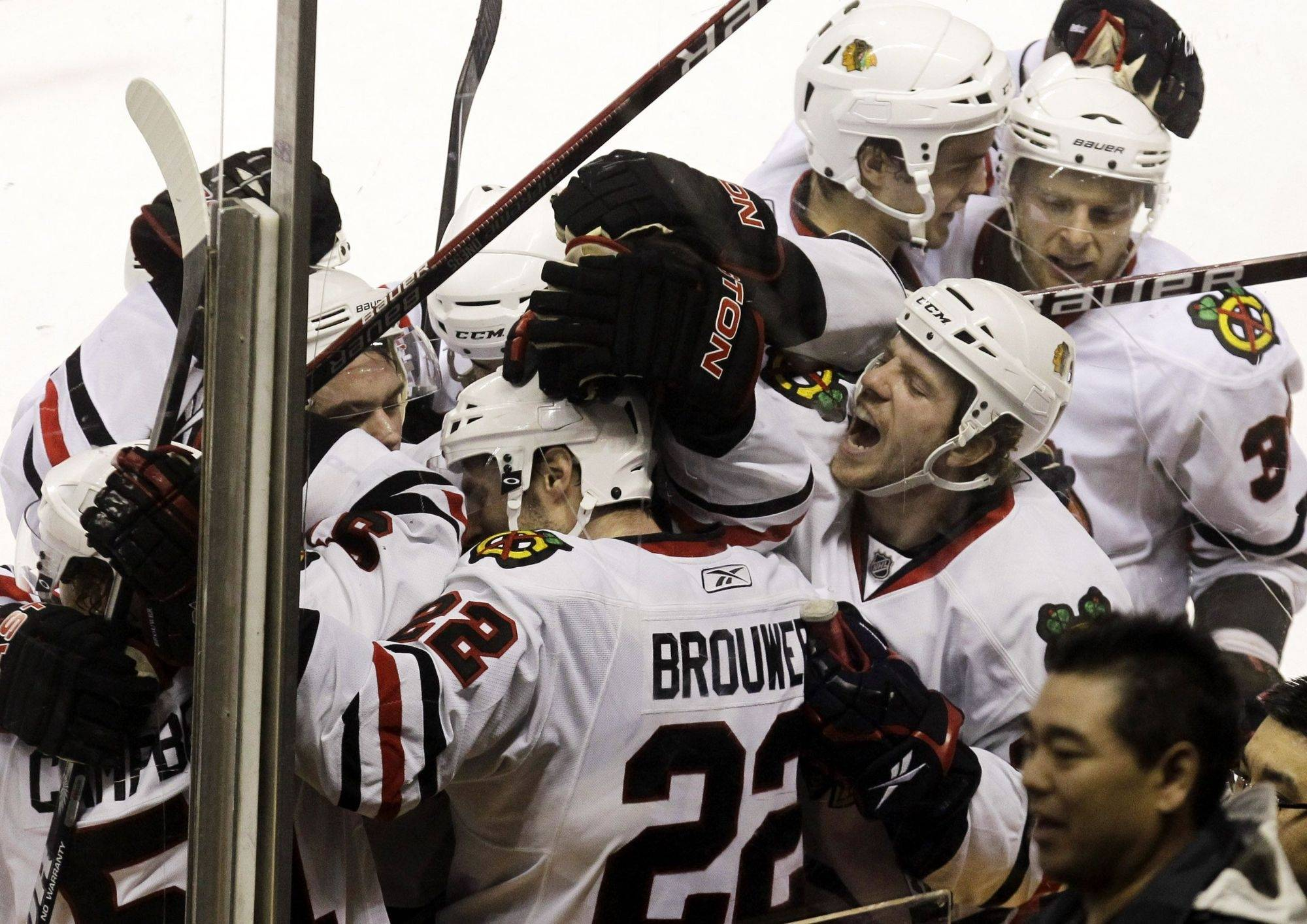 Troy Brouwer is mobbed by Blackhawks teammates after scoring in overtime to beat the Sharks 4-3 on Thursday night.