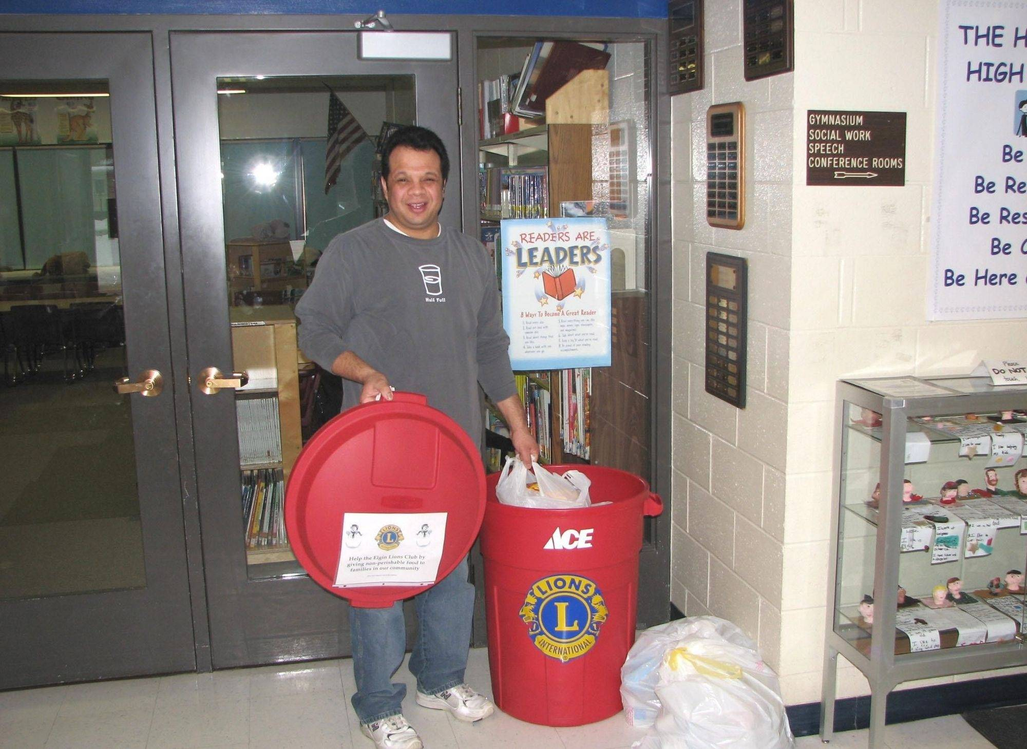 Carlos Trujillo, home school liaison administrator at Highland Elementary School, shows off the Elgin Lions Club collection bin for nonperishable food donations.