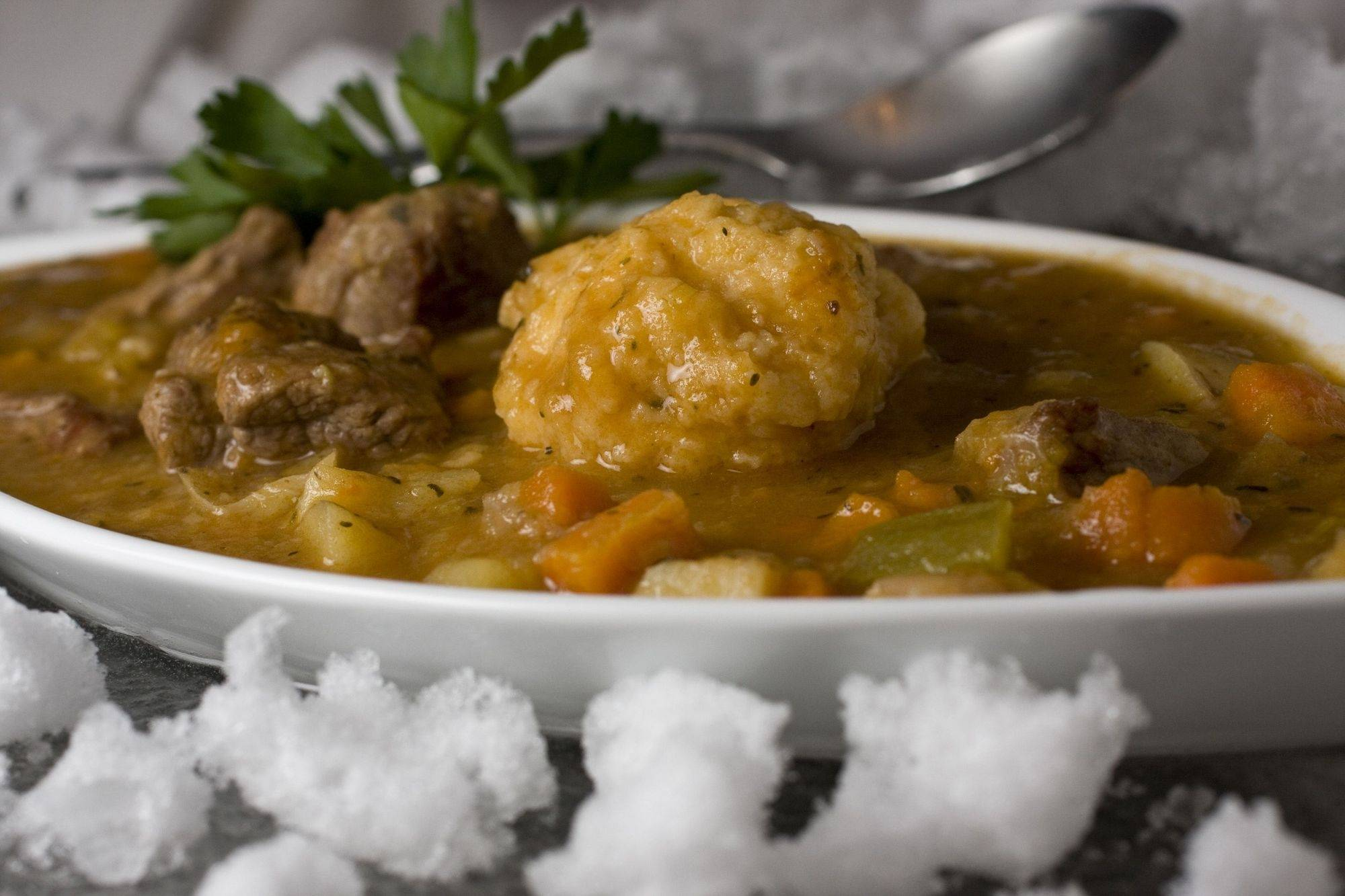 A large dumpling sits like a curling stone on the ice when serving this three-onion lamb stew with dumplings.
