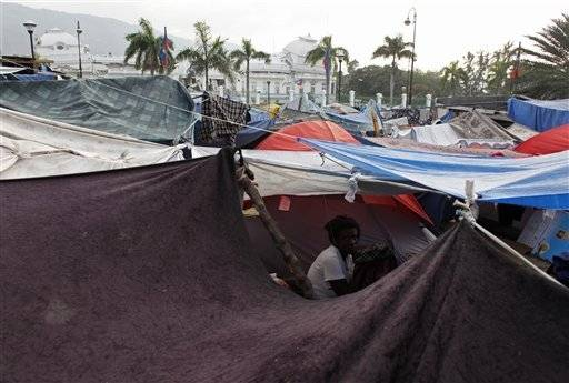 A woman sits under a tarp in a makeshift tent camp for earthquake survivors outside the collapsed National Palace, behind, in Port-au-Prince, Friday. A half-million Haitians who fled their shattered capital after the earthquake are starting to return.