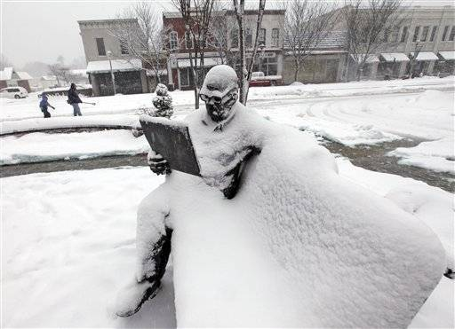 Pedestrians struggle through the snow behind a statue of a man reading in front of the Public Library during a major winter storm in Ashland, Va., Saturday.