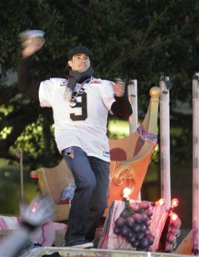 New Orleans Saints quarterback Drew Brees tosses beads to the crowd as the team does a victory parade through the central business district of New Orleans, Tuesday,