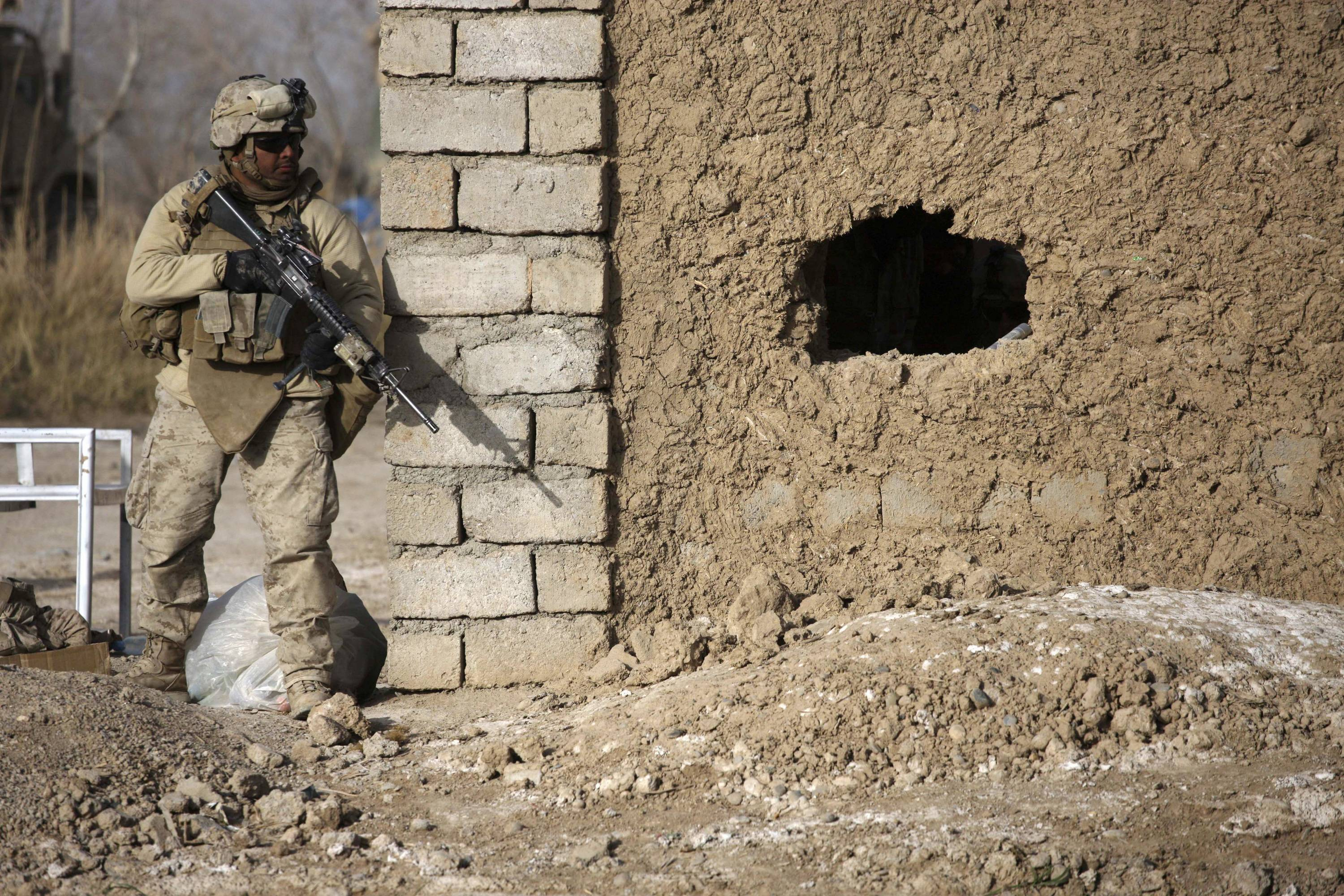 A U.S. Marine helps provide security as a U.S. Army flight medic with Task Force Pegasus evacuates two Marine casualties from the battlefield, in Marjah, Helmand province, southern Afghanistan.