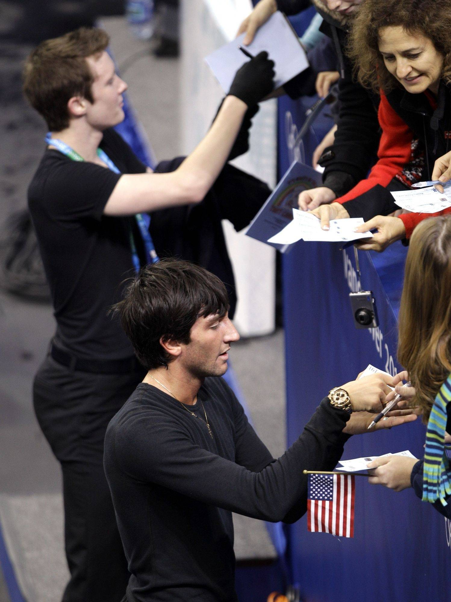 Evan Lysacek and Jeremy Abbott sign autographs for fans after Monday's practice.
