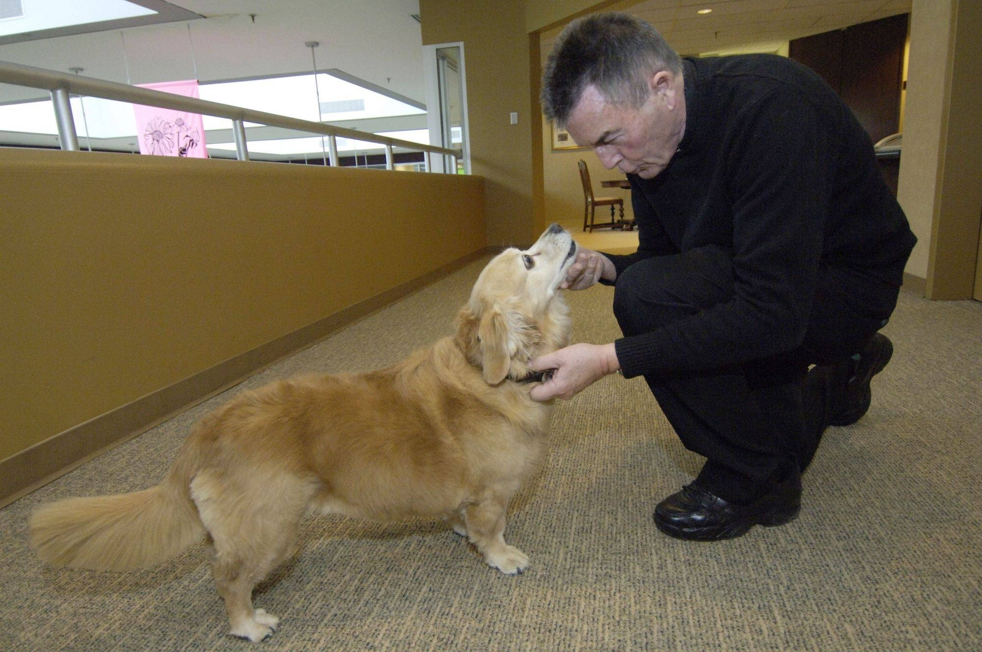 Br. Jim Classon of the Alexian Brothers stops to pet Mitzi as they go about their daily work routine.