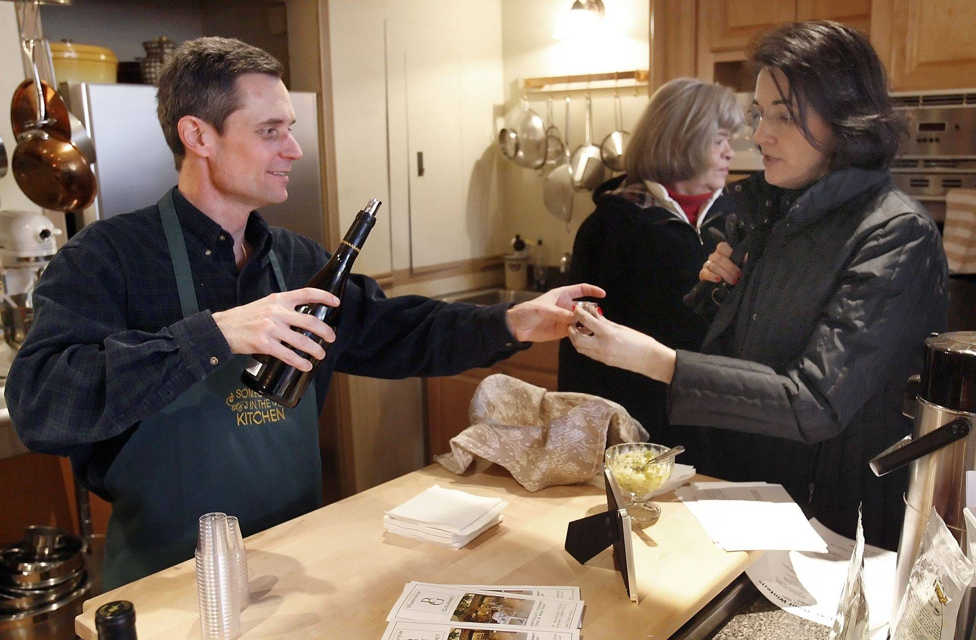 "Kevin Potrzeba of Someone's in the Kitchen serves a sample of Pinot Noir to Sharon Leinbach of Libertyville at a previous ""Let's Wine About Winter"" event."