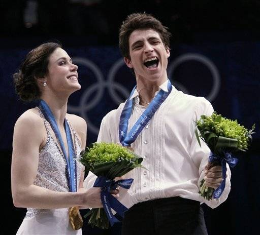 Canada's Tessa Virtue and Scott Moir react on the podium after winning the gold medal in the ice dance figure skating competition at the Vancouver 2010 Olympics in Vancouver, British Columbia, Monday.
