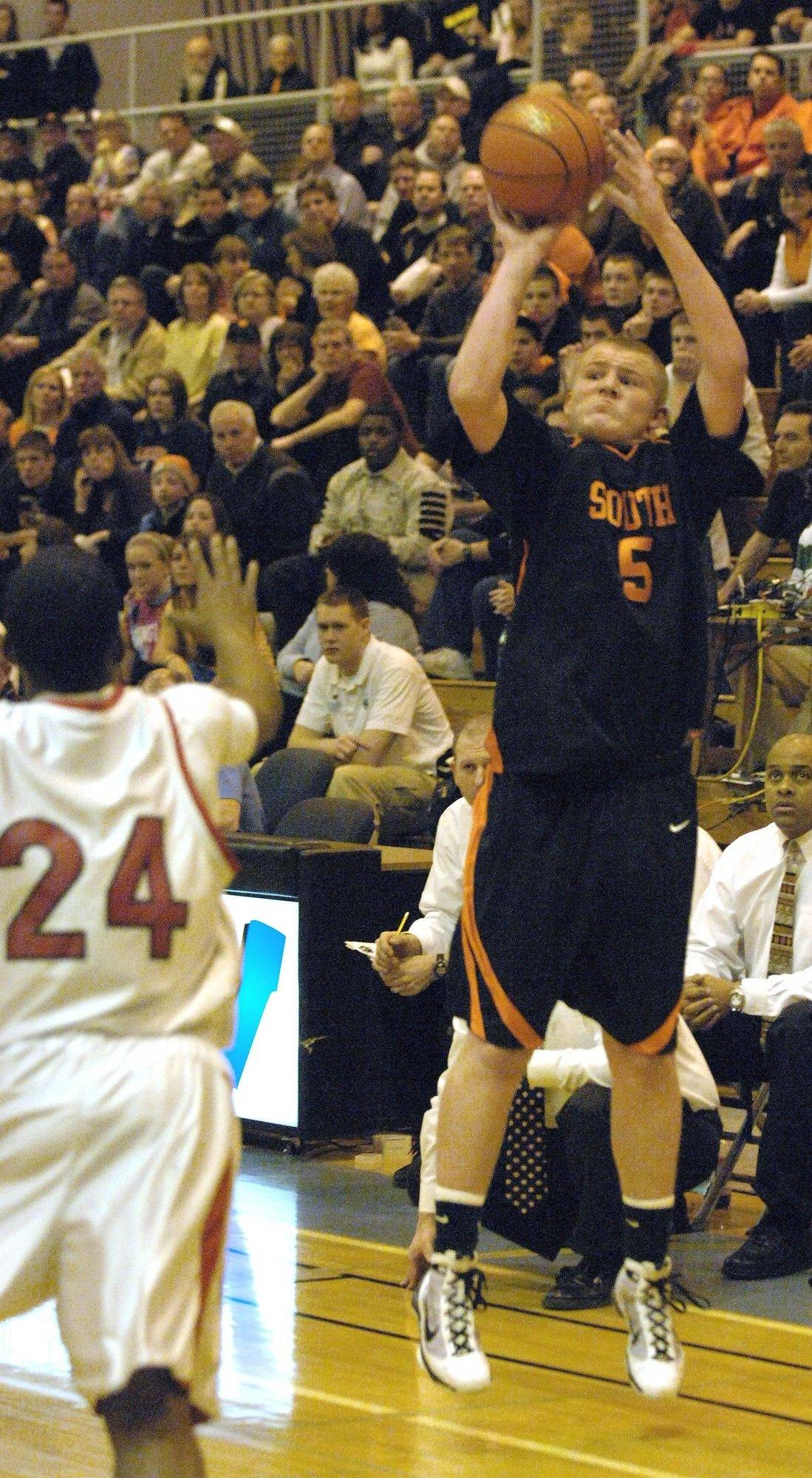 Reilly O'Toole of Wheaton Warrenville South goes up for a shot over Devin Parks of Glenbard East.
