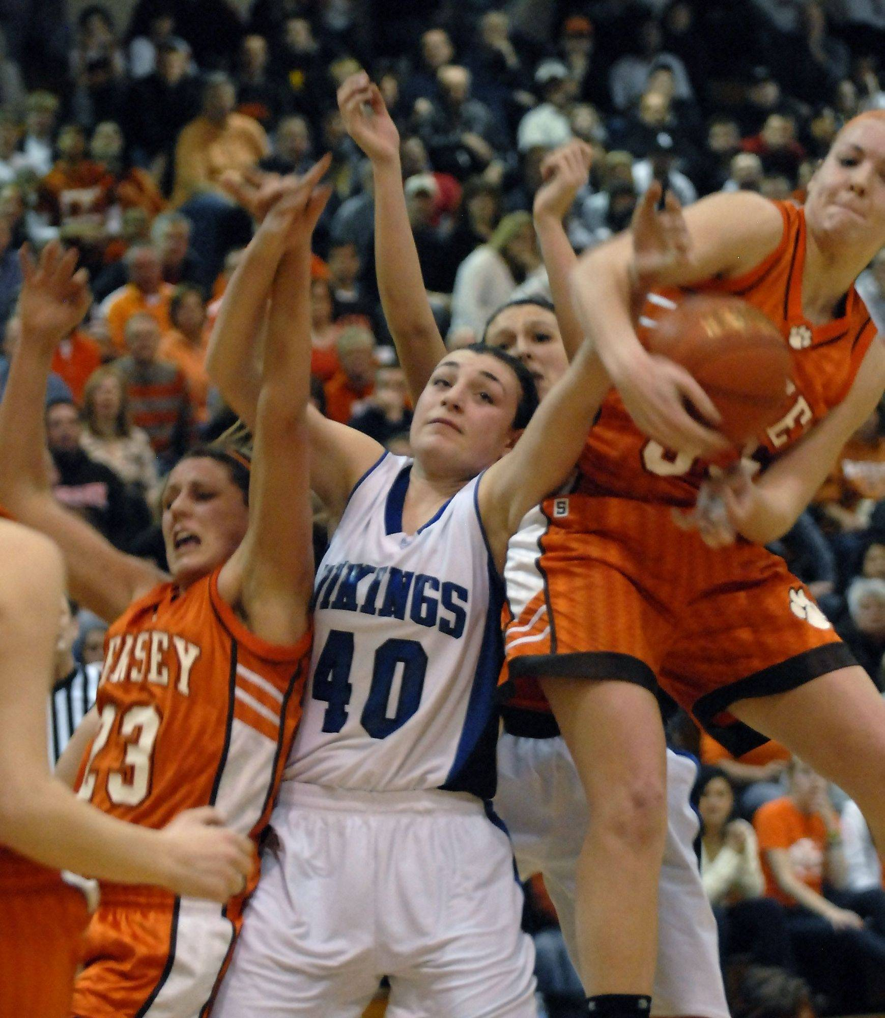 Hersey's Kathryn Korff, 23, and Maddie Swan,33, fight for a rebound against Geneva's Lauren Wicinski, 40, at the Streamwood Class 4A girls basketball supersectional.