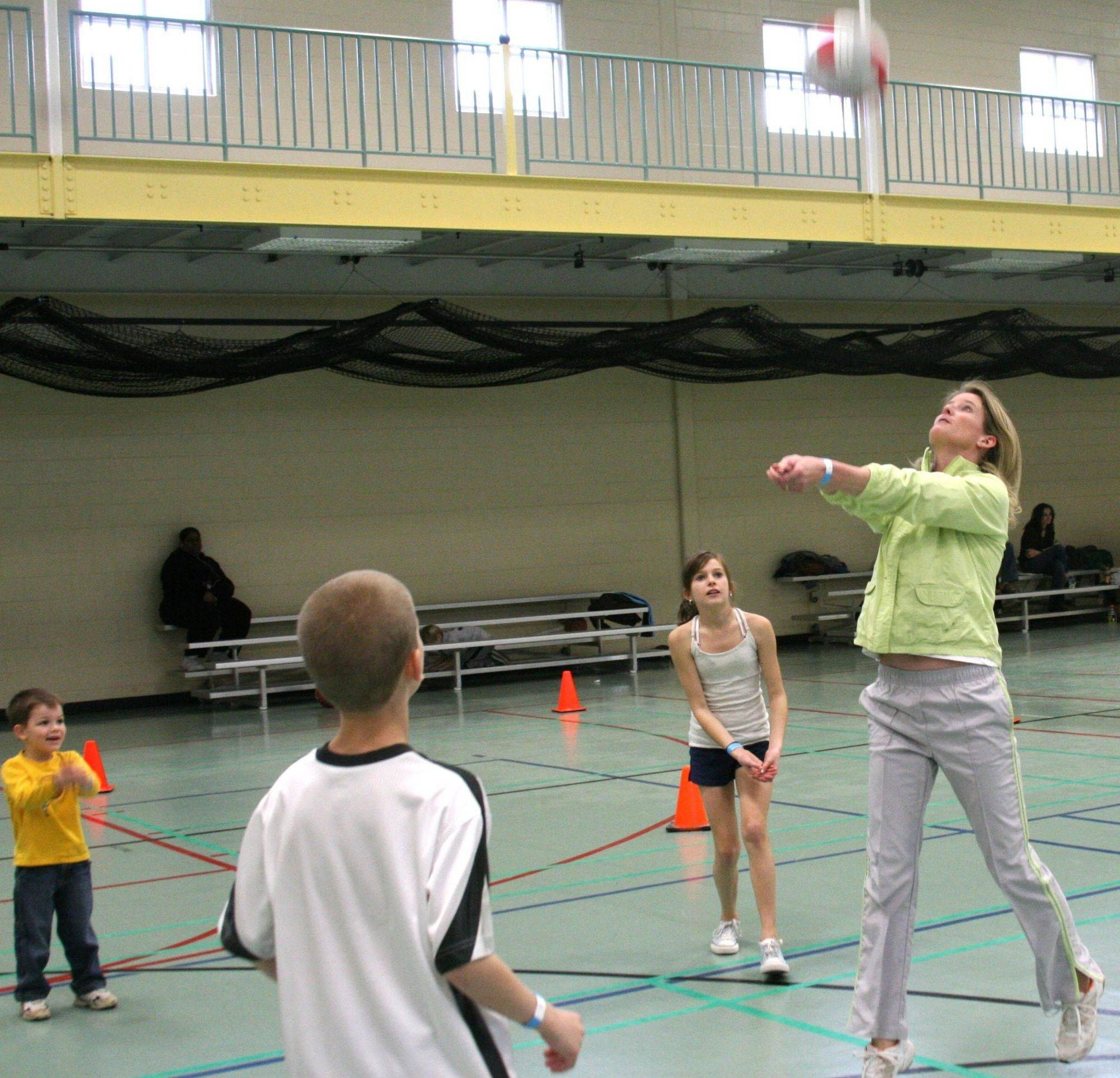 Karin Myre, right, provides a demonstration of the bump for aspiring volleyball players Benjamin Schwieger, Daniel Schwieger, back, and Stephanie Schwieger during a recent family open gym at the Eola Community Center.