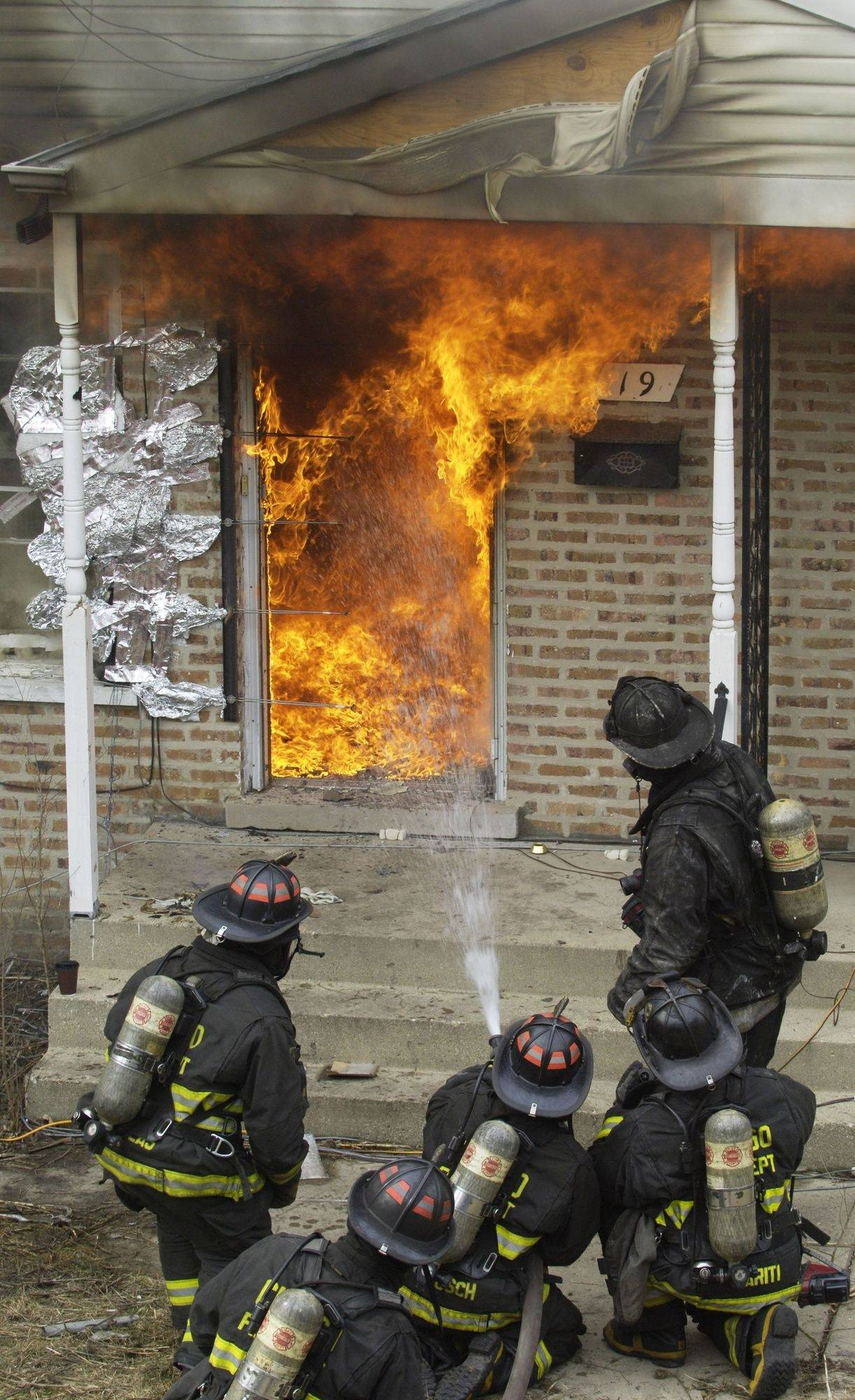 Firefighters extinguish a controlled burn in a vacant Bensenville townhouse Friday as part of a training exercise for both firefighters and fire investigators.
