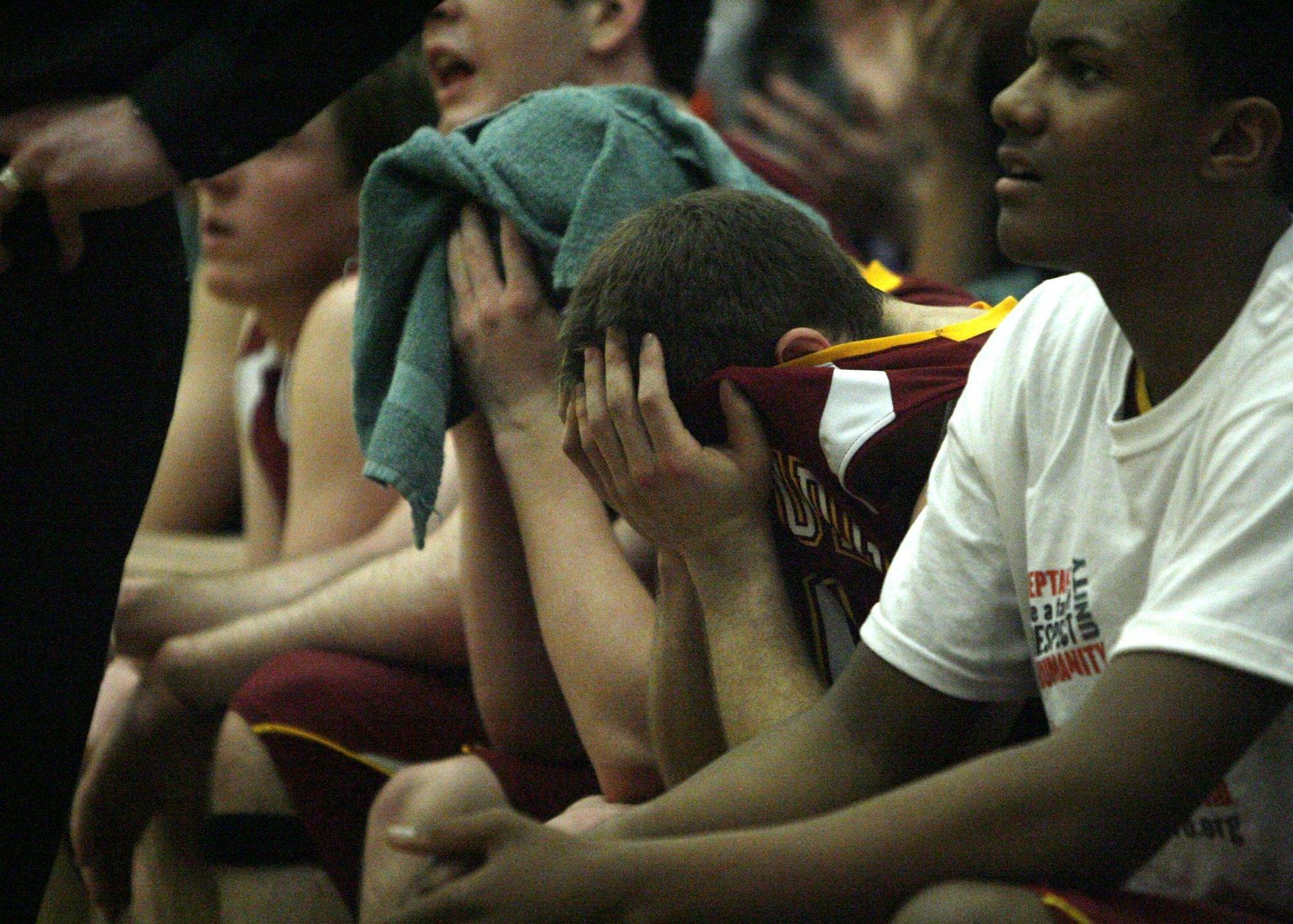 The Schaumburg bench can't bear to look at the score during the closing minutes of their loss to Waukegan in the Class 4A Waukegan boys basketball sectional final Friday in Waukegan.