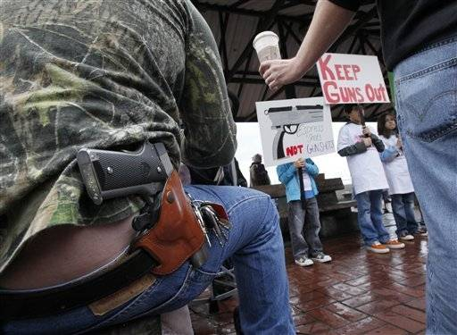 Greg Dement is handed a Starbucks coffee drink as he sits with a handgun strapped to his belt while looking on at an anti-gun rally in Seattle.