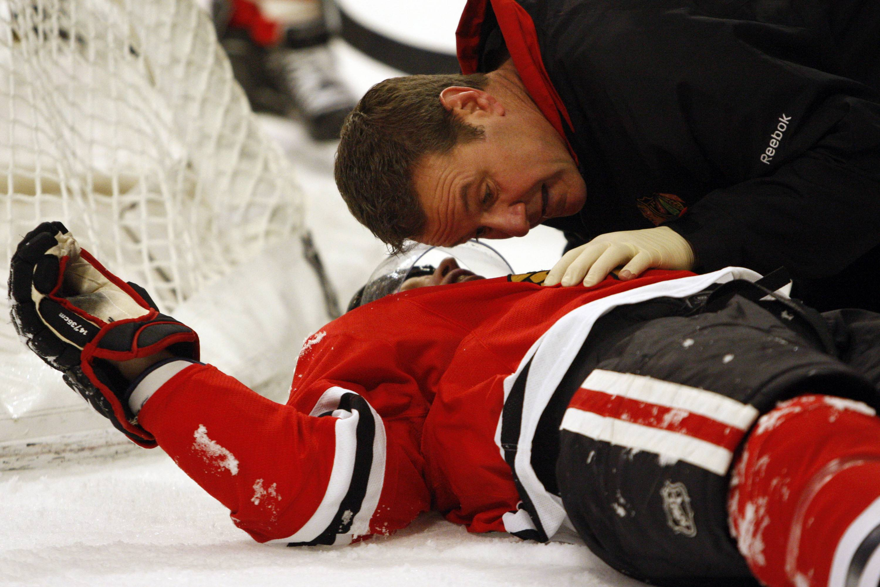 Trainers tend to Blackhawks defenseman Brian Campbell after he was drilled into the boards during the first period.