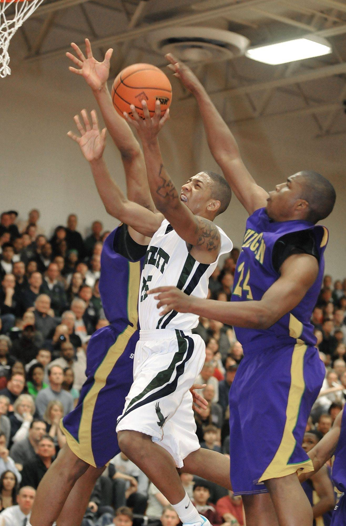 Bartlett's Mike Banks tries to break through Waukegan's Jereme Richmond and Quan Connor in supersectional game on Tuesday, March 16.