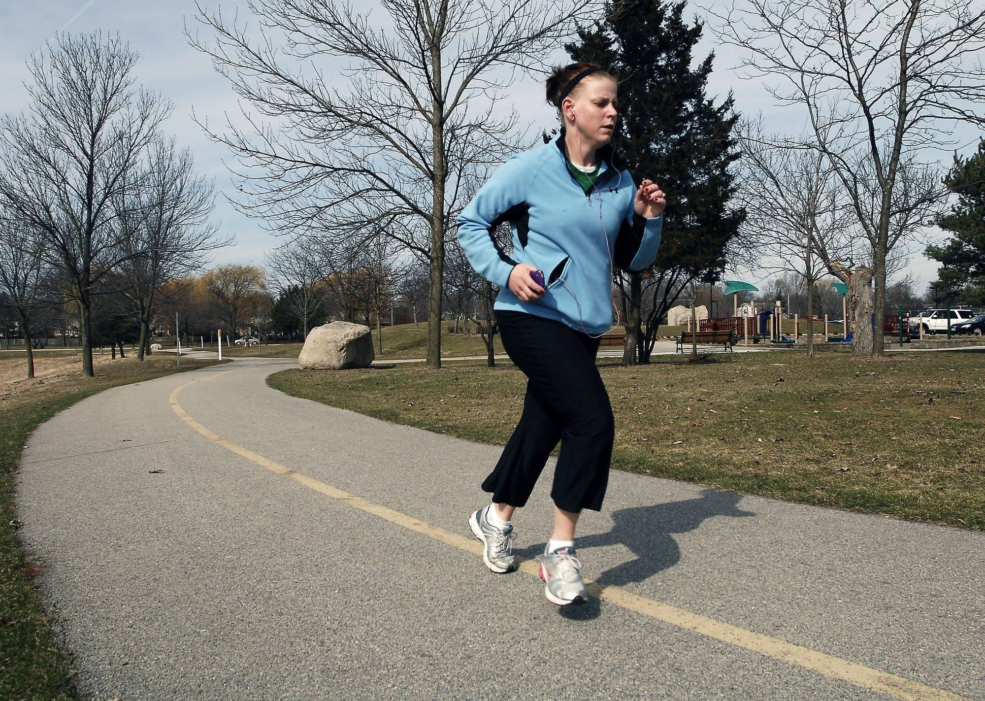 Jeanne Brock of Mount Prospect takes advantage of Thursday's warm weather to train at Lake Arlington for the Shamrock Shuffle run on Sunday in Chicago. Unfortunately Sunday's forecast is calling for a high in the 30s with a chance of snow.