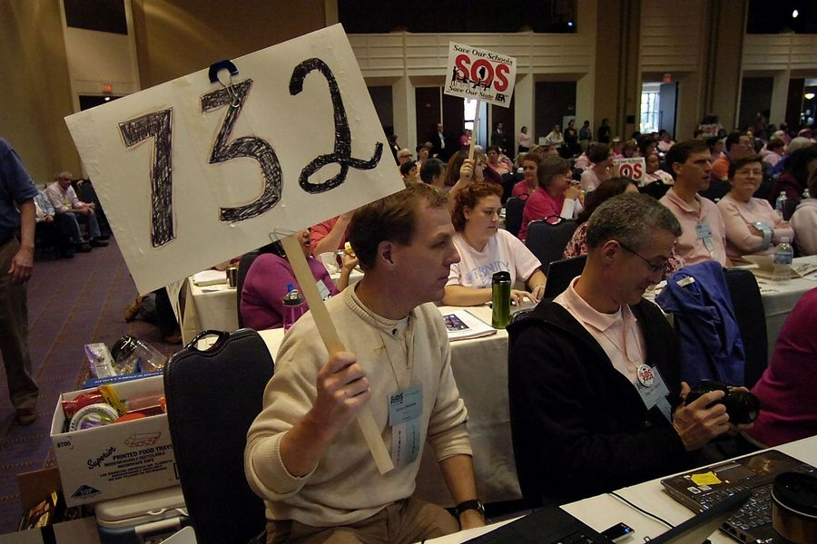 U-46 sixth-grade teacher Steve Olofson holds a sign showing how many teachers were laid off from his Elgin-based district as he listens to Gov. Quinn speak in Rosemont on Friday.