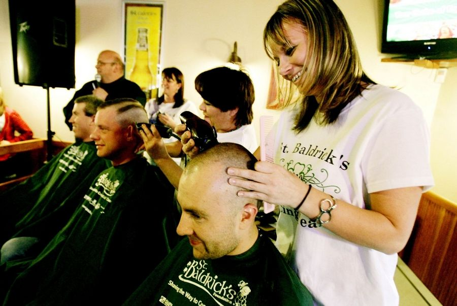 Hair stylist Kelly Wirtanen shaves the head of West Chicago police officer Waylon Potts during a St. Baldrick's Day event Sunday. Potts was one of the event's co-organizers. The event was held at Hawthorne's Backyard Bar & Grill and raised more than $13,000.