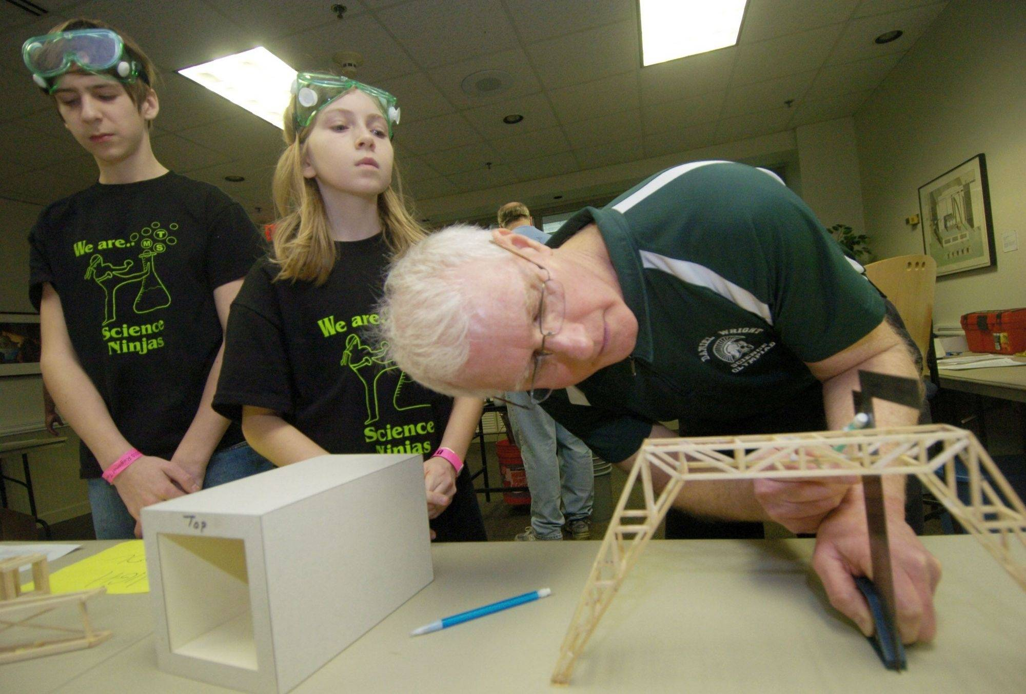 Katherine Jaffe looks over the shoulder of volunteer Al Buckardt while Matthew Kosk waits, as the sixth graders from Thomas Middle School in Arlington Heights have their bridge measured during Saturday's Science Olympiad at College of Lake County.