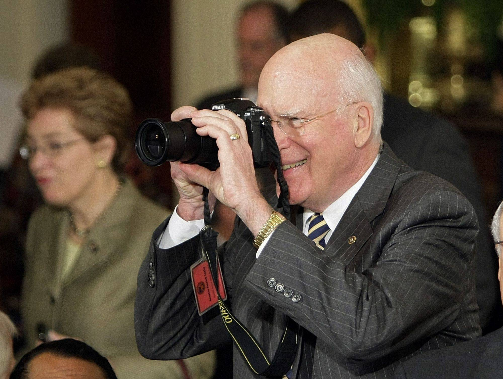 Sen. Patrick Leahy, D-Vt., photographs the scene and dignitaries as they arrive for the signing of the health care bill.