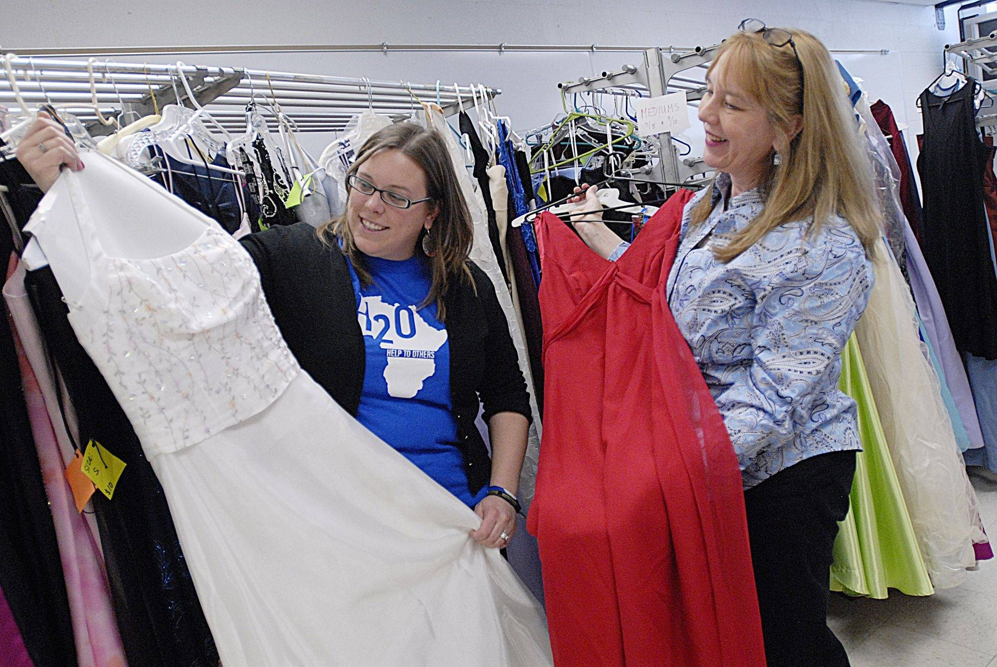 "Antioch Community High School teachers Kerri Elliott, left and Donna Corcoran look over some of the 300 dresses that will be for sale in the ""Prom On A Dime"" fundraising event set for next month."
