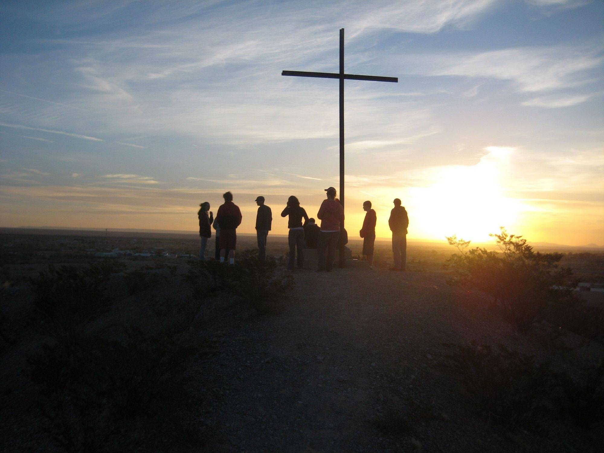 A silhouette of a group of tourists near a cross on top of a hill at sunrise in Guadalupe, Mexico.