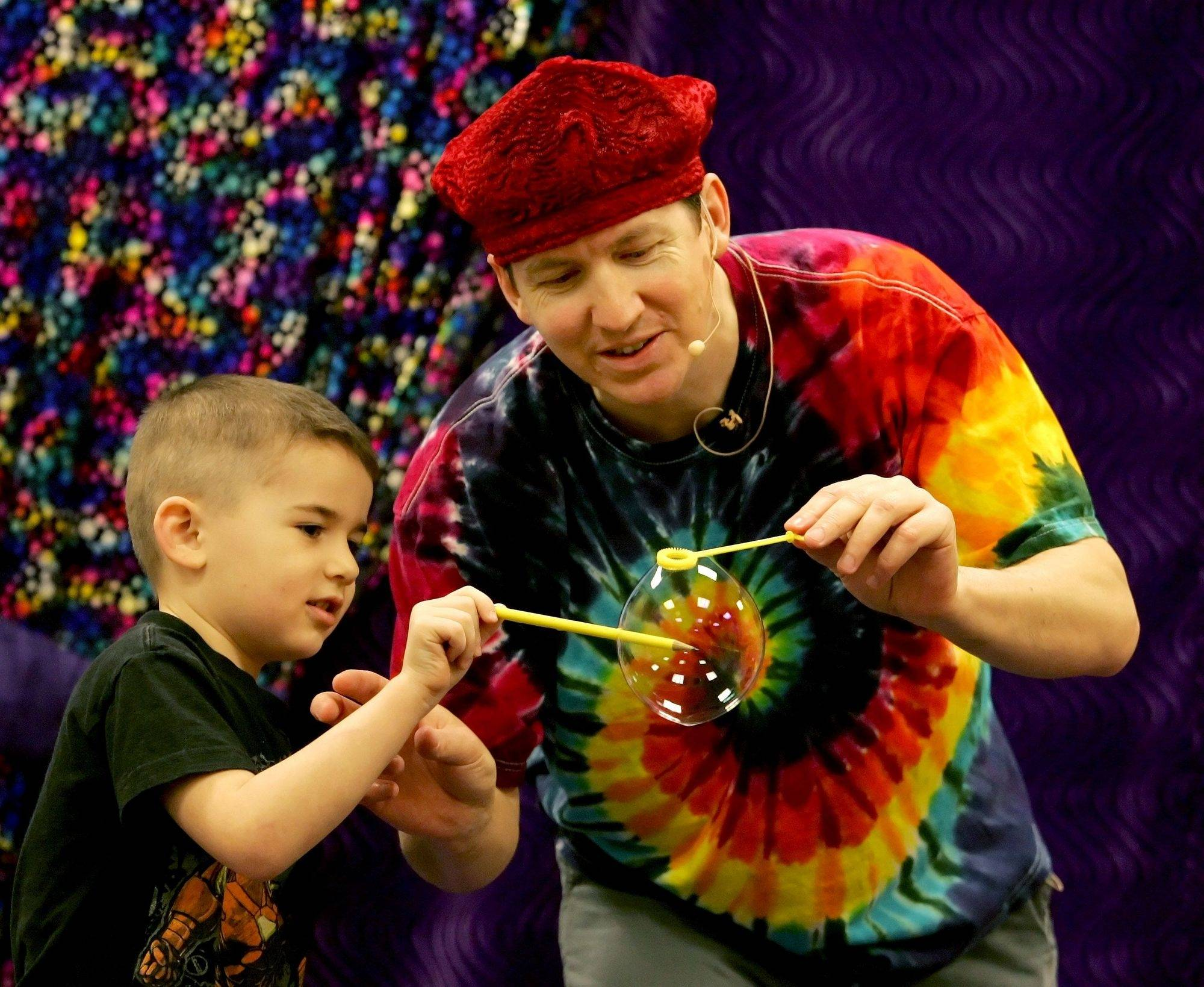 Geoff Akins and 4-year-old Lachlan Sorensen demonstrate how you can insert a pencil into a bubble without popping it - if you know what you're doing. Akins, known as The Bubble Man, recently performed at Prairie Children Preschool in Aurora.