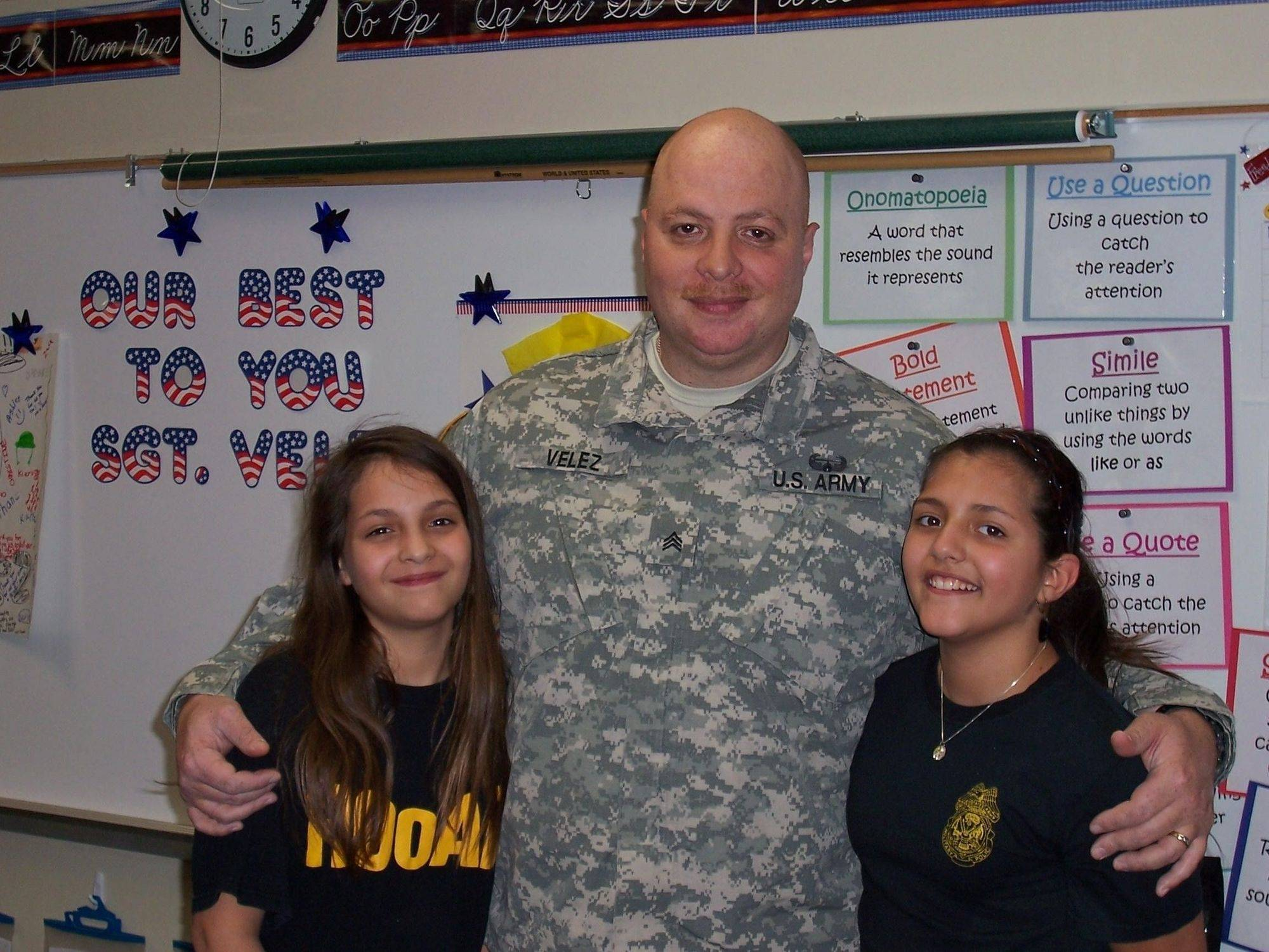 "Sergeant Otilio Velez joins with his twin daughters Taylor, left, and Lauren at ""Red, White, and Blue Send-Off"" held at Martin Elementary School."