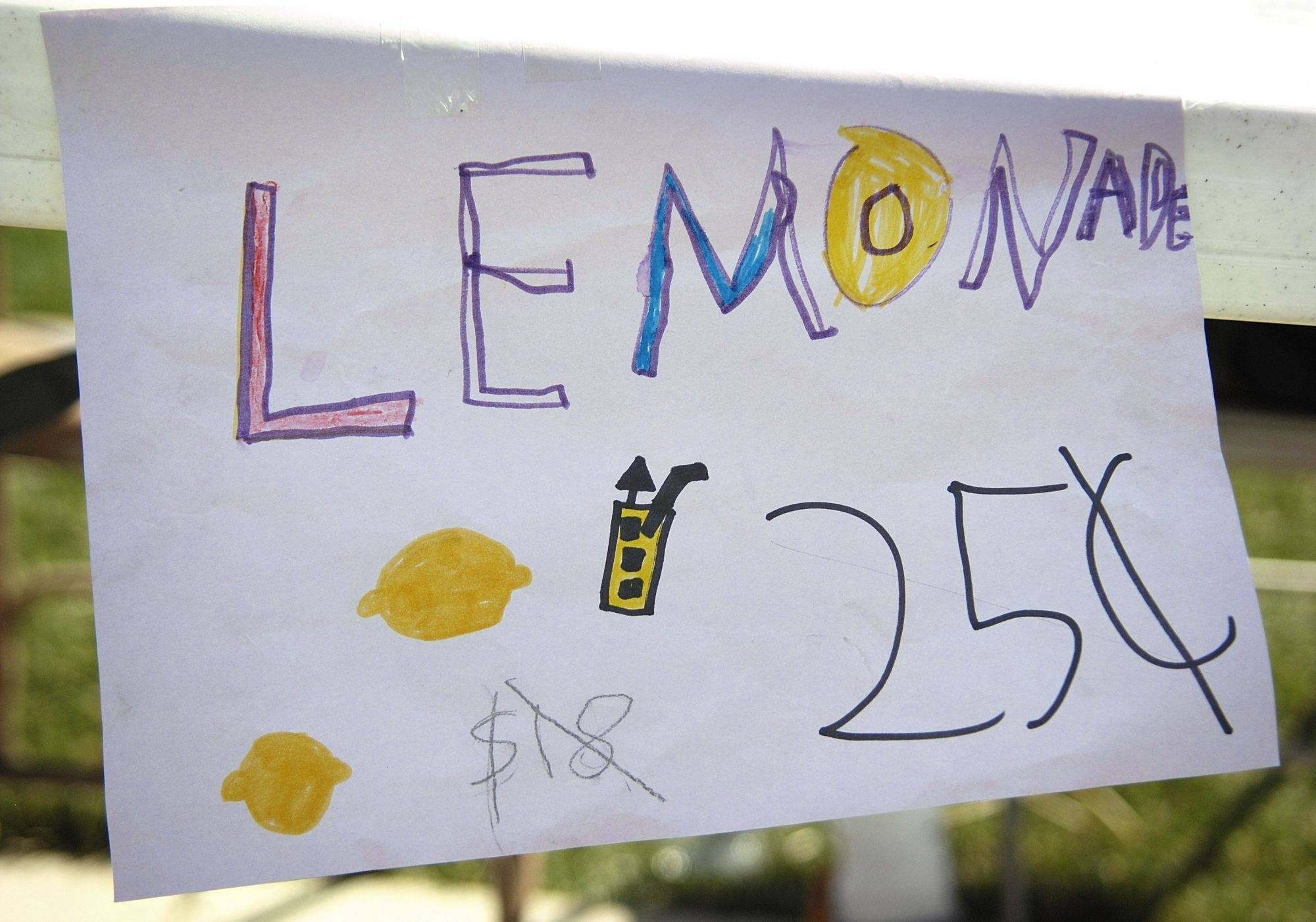 A slightly askew sign for lemonade hangs from Mason Micka's stand on Stoffa Avenue in Elburn Wednesday. The drink was available for a bargain price of 25 cents, down from $18, according to the sign. Mason's good sense of humor brought in $7.05.