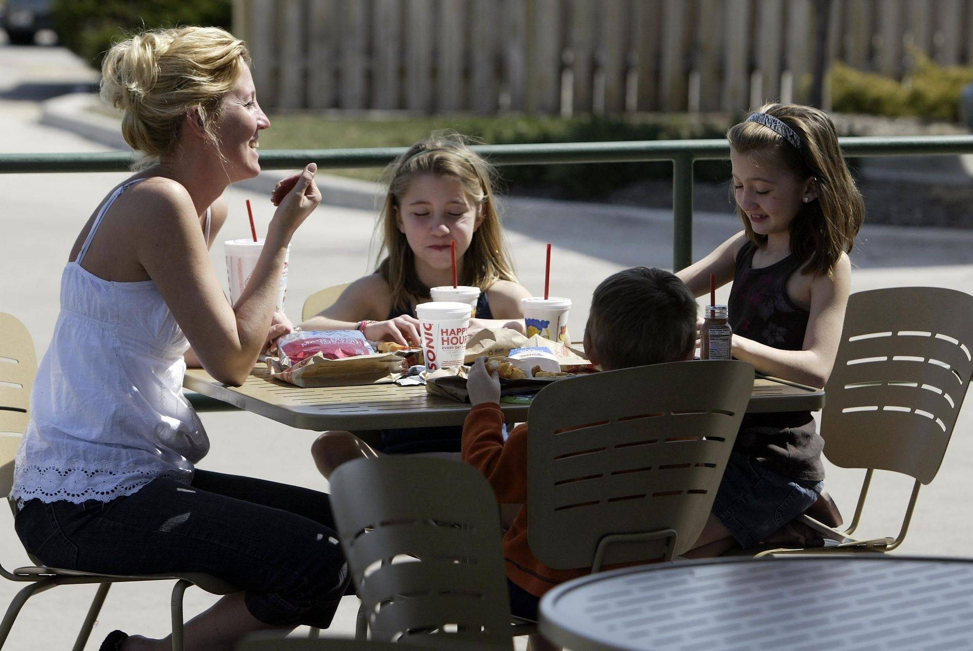 """It's a nice break, it's awesome"" says Staci Swadener of Bartlett, as she enjoys lunch with her children Sara, 9, middle, Anna, 9, right, and Luke, 3, at Sonic in Bartlett ."