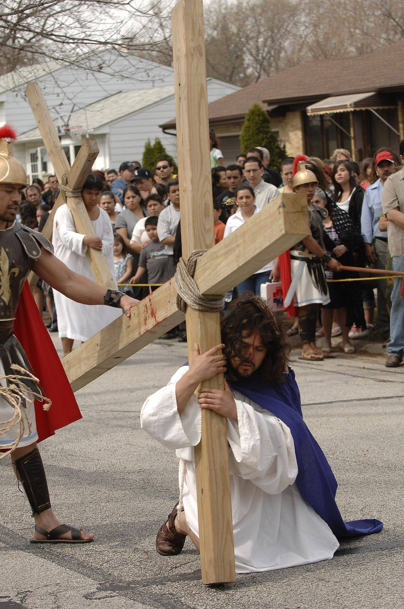 Jesus falls with his cross on Anderson Drive Friday in Palatine during the annual re-enactment of the crucifixion of Jesus Christ as performed by members of Mision San Juan Diego in Arlington Heights.