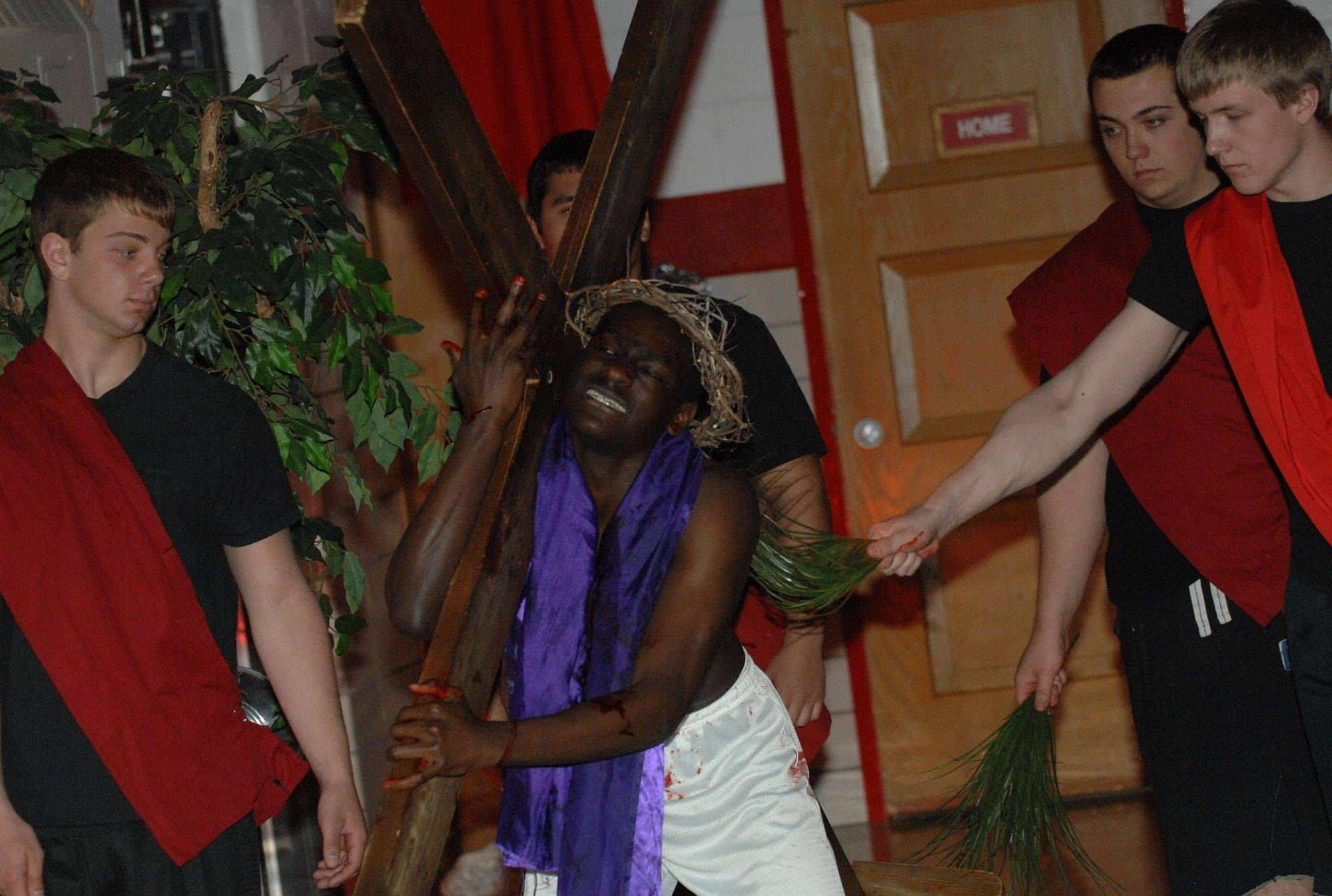 James Connelly as Jesus carries the cross while soldiers whip him during The Passion of Jesus Christ performed at St. Alexander's Church in Villa Park.