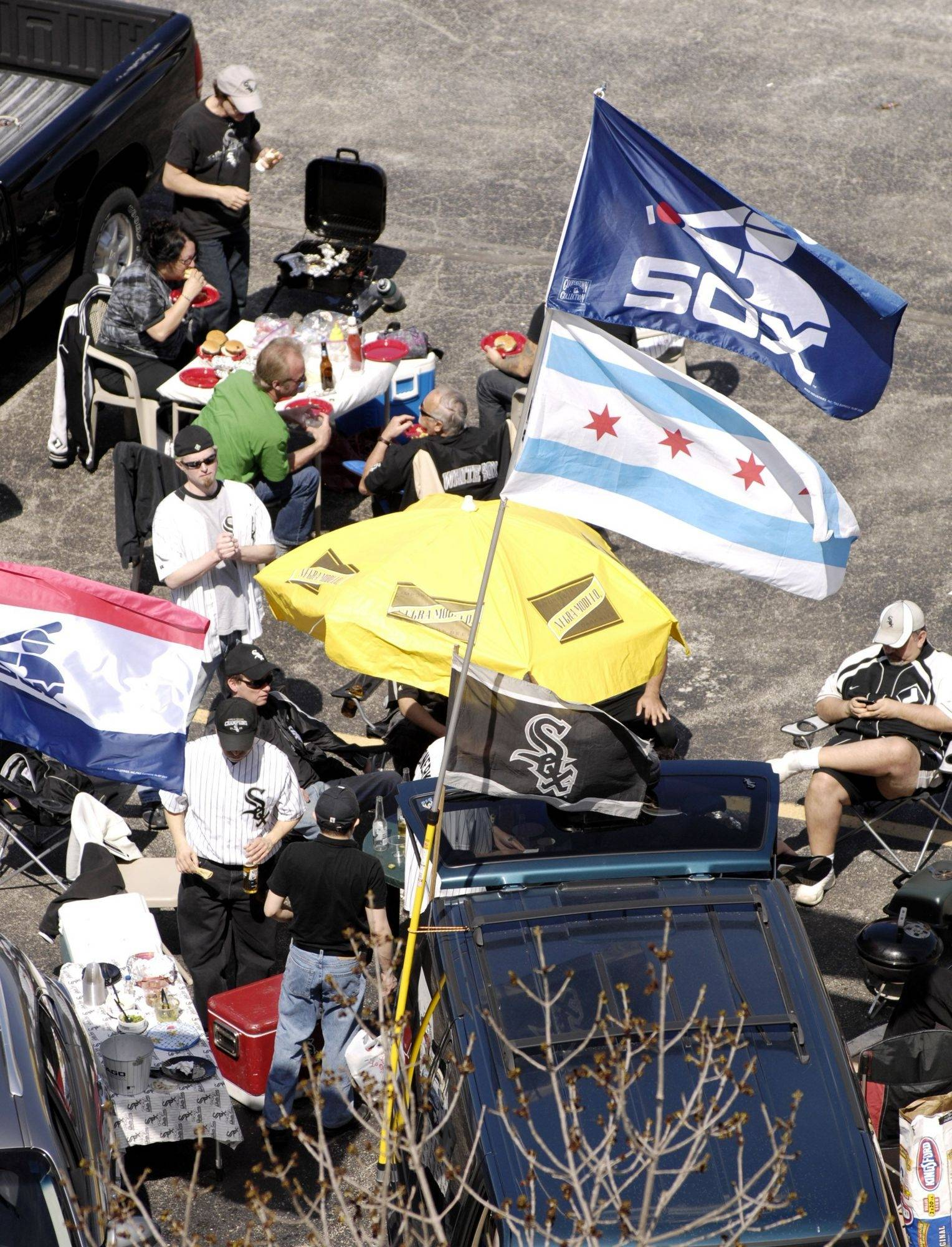 Flags flap in the breeze as tailgaters dine before the Chicago White Sox kick off the season with their home opener against the Cleveland Indians.