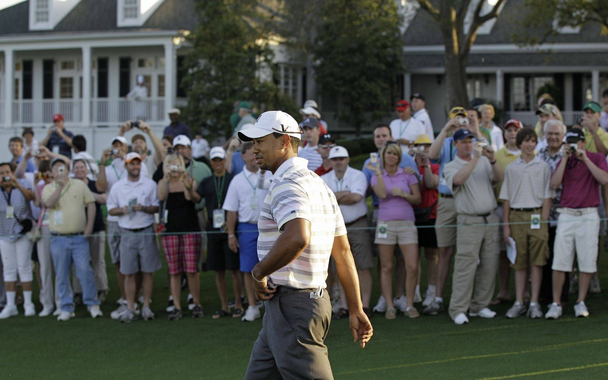 Spectators take photos as Tiger Woods walks down the first fairway during a practice round for the Masters golf tournament in Augusta, Ga. on Monday. The tournament begins.