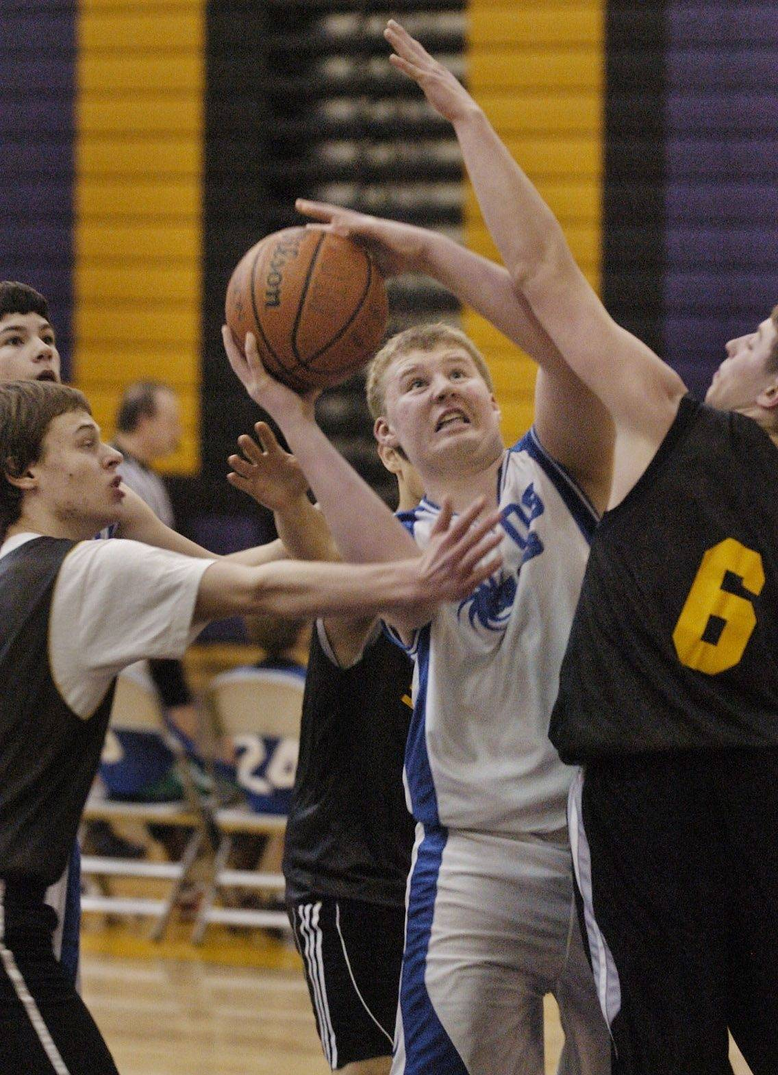 Eighth-grader Chase Mangioni, center, of the Wauconda Cylones battles for a bucket against the team from Elgin Homeschool during a charity basketball tournament hosted by the Wauconda Cyclones basketball teams at Wauconda High School.