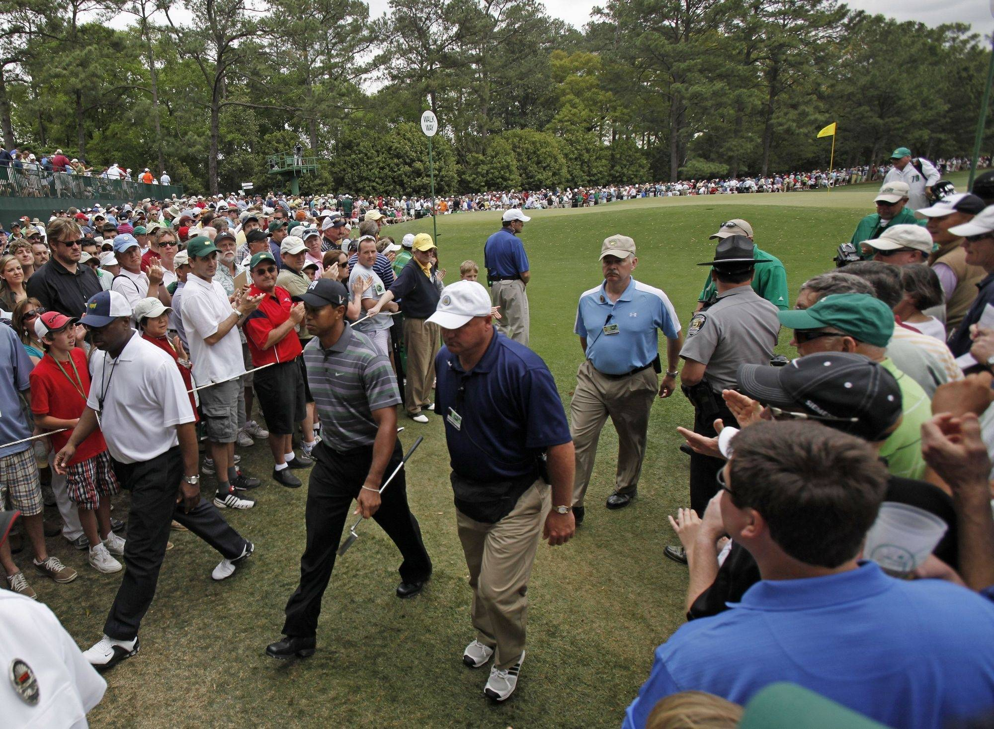 Escorted by security personnel, Tiger Woods walks to the second tee during the first round of the Masters .