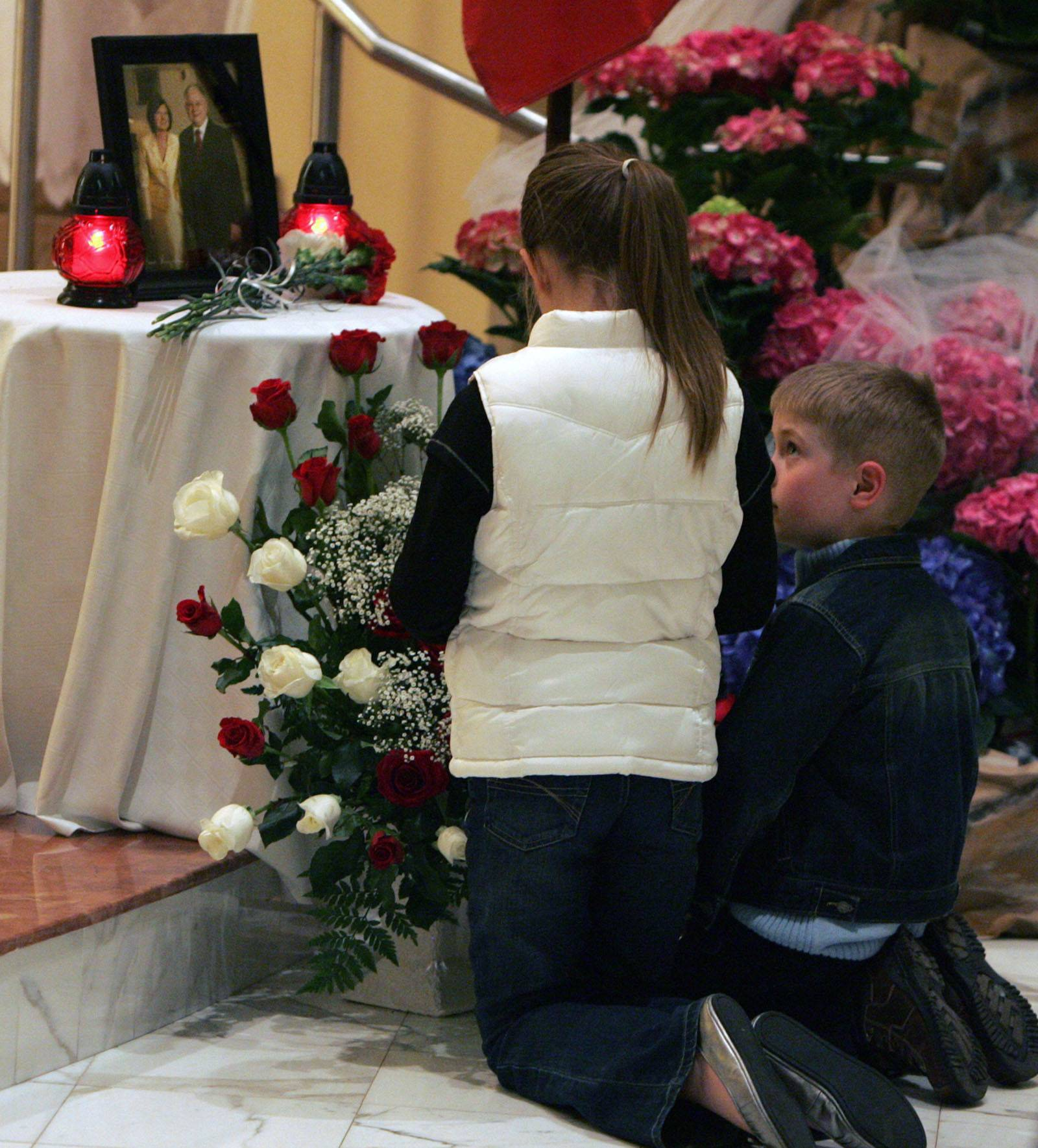 Victoria Szczudrawa, 10, and her bother Jacob, 6, pray at a photograph of Polish President Lech Kaczynski and his wife during a memorial Mass at Divine Mercy Polish Mission in Lombard on Saturday.
