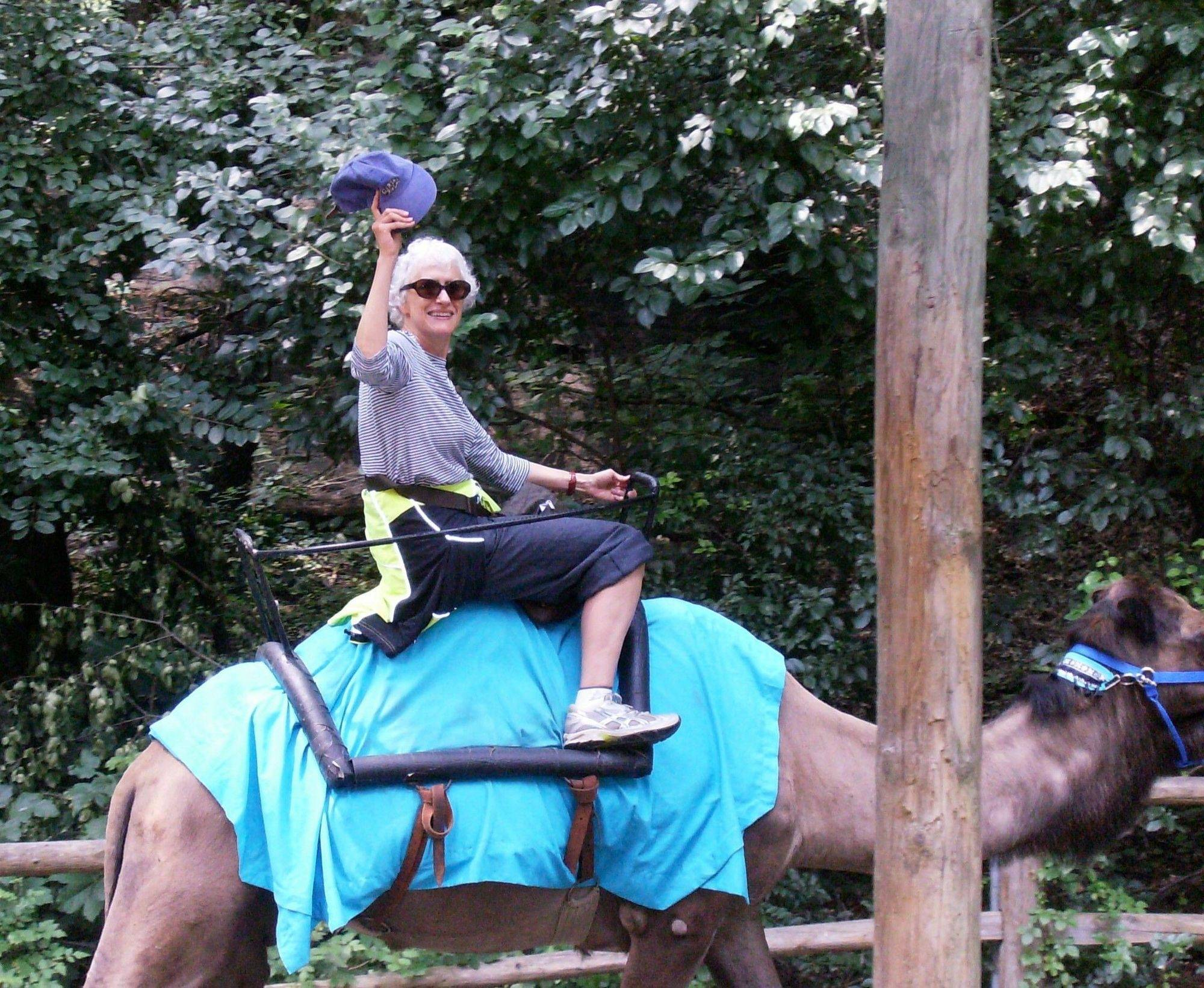 When author Sara Paretsky is not writing she is fun-loving, even if that means riding a camel at the Bronx Park Zoo in New York City.