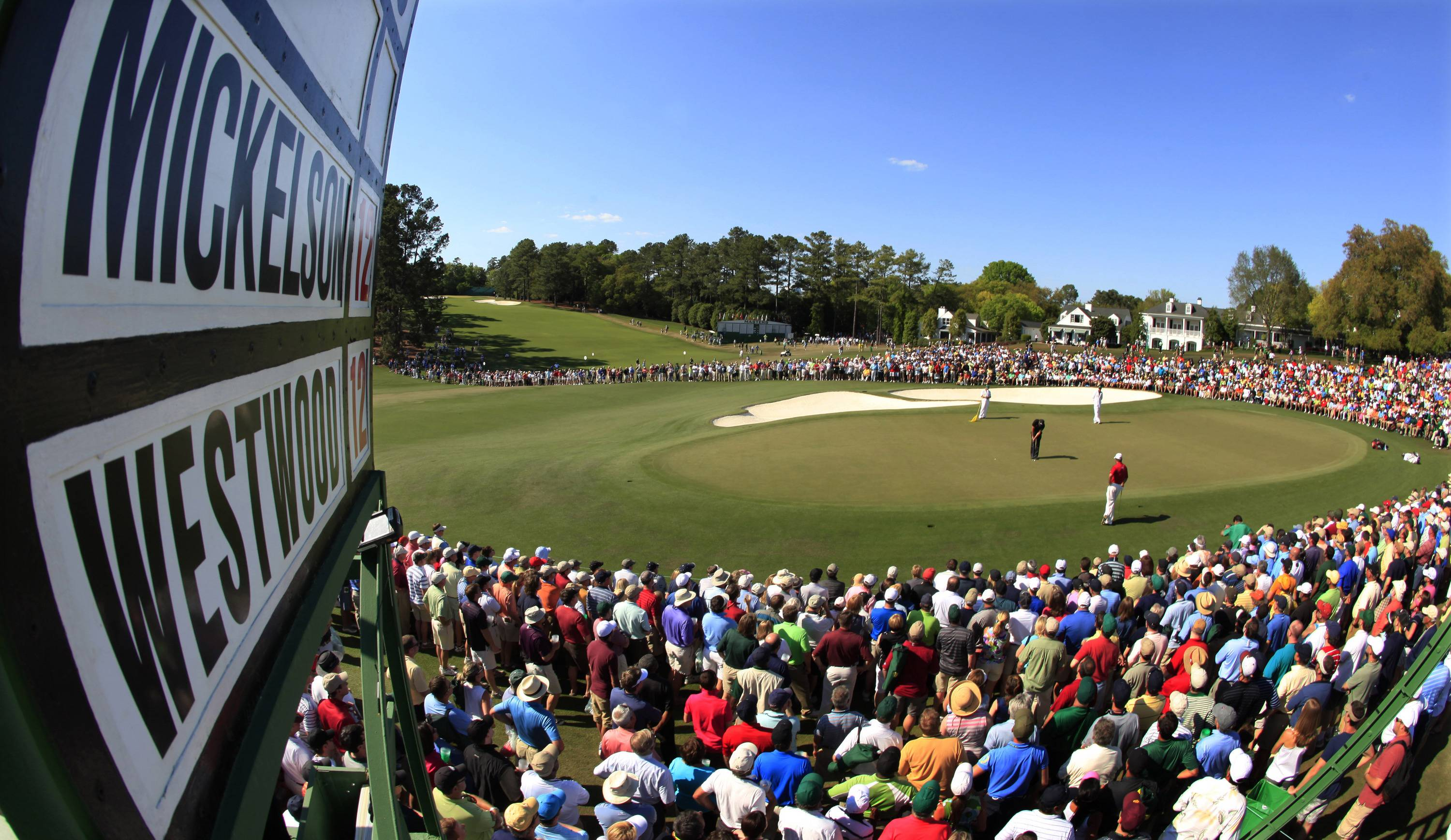 Lee Westwood, right, of England watches as Phil Mickelson putts on the ninth green during the final round of the Masters.