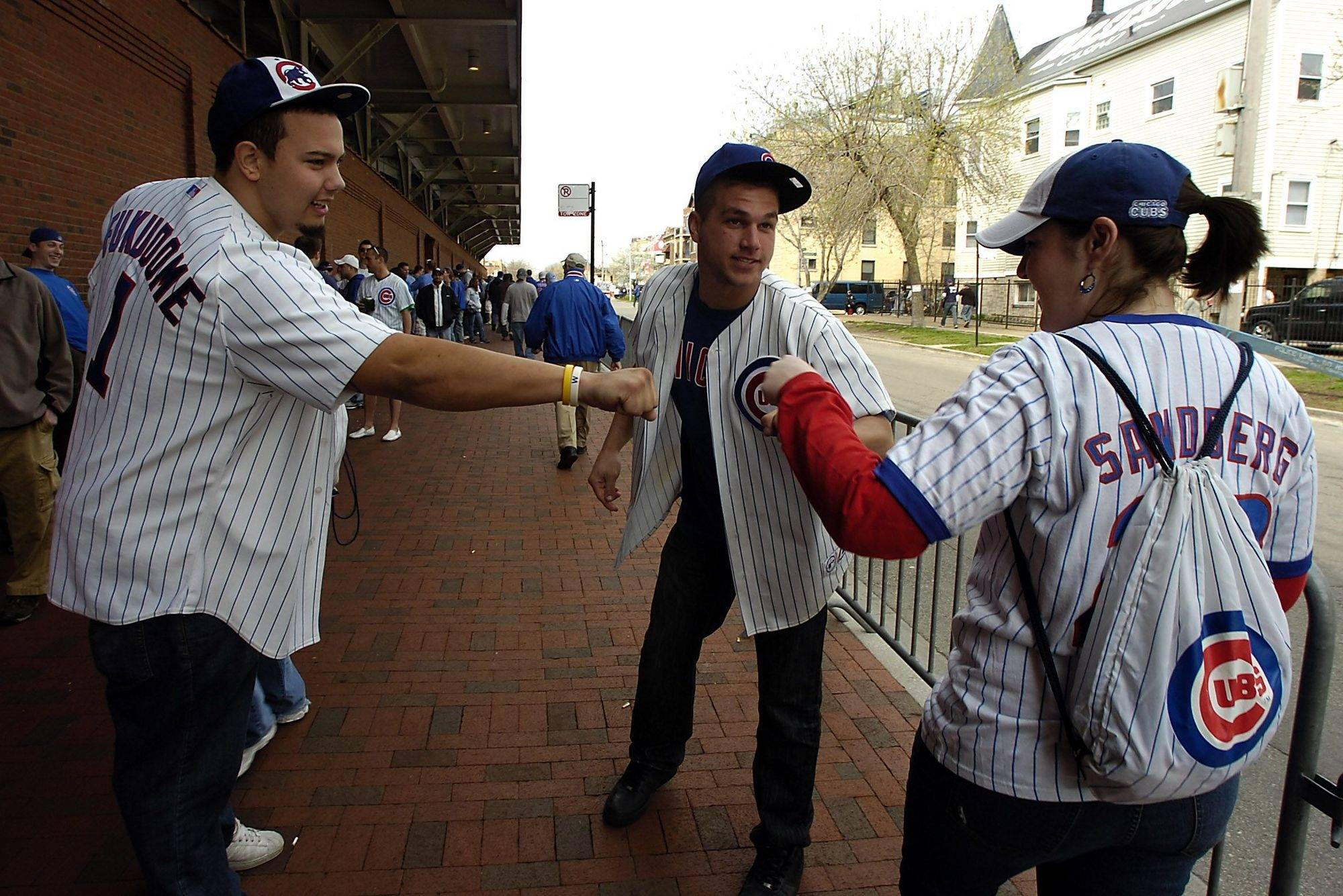 Happy Cubs fans Tim O' Connor and Lance Dobler, both of Elgin, bump fists with any and all Cubs fans that crossed their path as they waited to the gates to open at Wrigley Field on Monday.